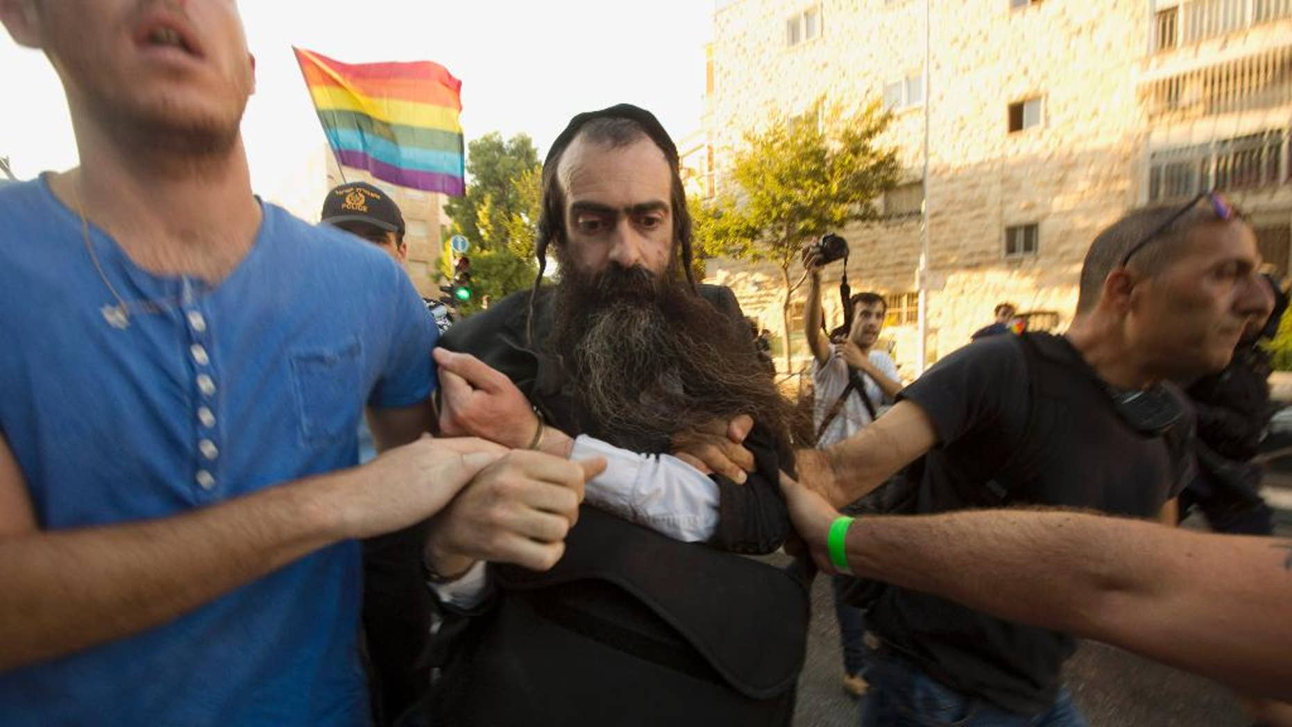 FILE - In this Thursday, July 30, 2015 file photo, ultra-Orthodox Jew Yishai Schlissel is detained by plain-clothes police officers after he stabbed people during a gay pride parade in Jerusalem. An Israeli hospital spokeswoman said Sunday, Aug. 2, that a teenage girl stabbed by Schlissel, an anti-gay extremist, in Thursday's attack during the parade has died. (AP Photo/Sebastian Scheiner, File)