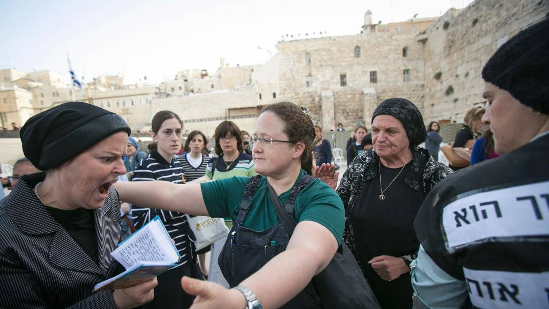 """FILE - In this June 9, 2013 file photo, an Israeli member of the """"Woman of the Wall"""" organization, right, tries to hug an ultra-Orthodox woman as they pray at the Western Wall, the holiest site where Jews can pray, in Jerusalem's old city. Israeli police say dozens of ultra-Orthodox Jews attacked buses bearing photos of women worshipping like men do. The advertisements on the buses were by Women of the Wall, a group that seeks to promote gender equality at Jerusalem's Western Wall, the holiest site where Jews can pray. The ads showed women and girls holding Torah scrolls, an act which many Orthodox Jews say is reserved for men. (AP Photo/Michal Fattal,File) ISRAEL OUT"""