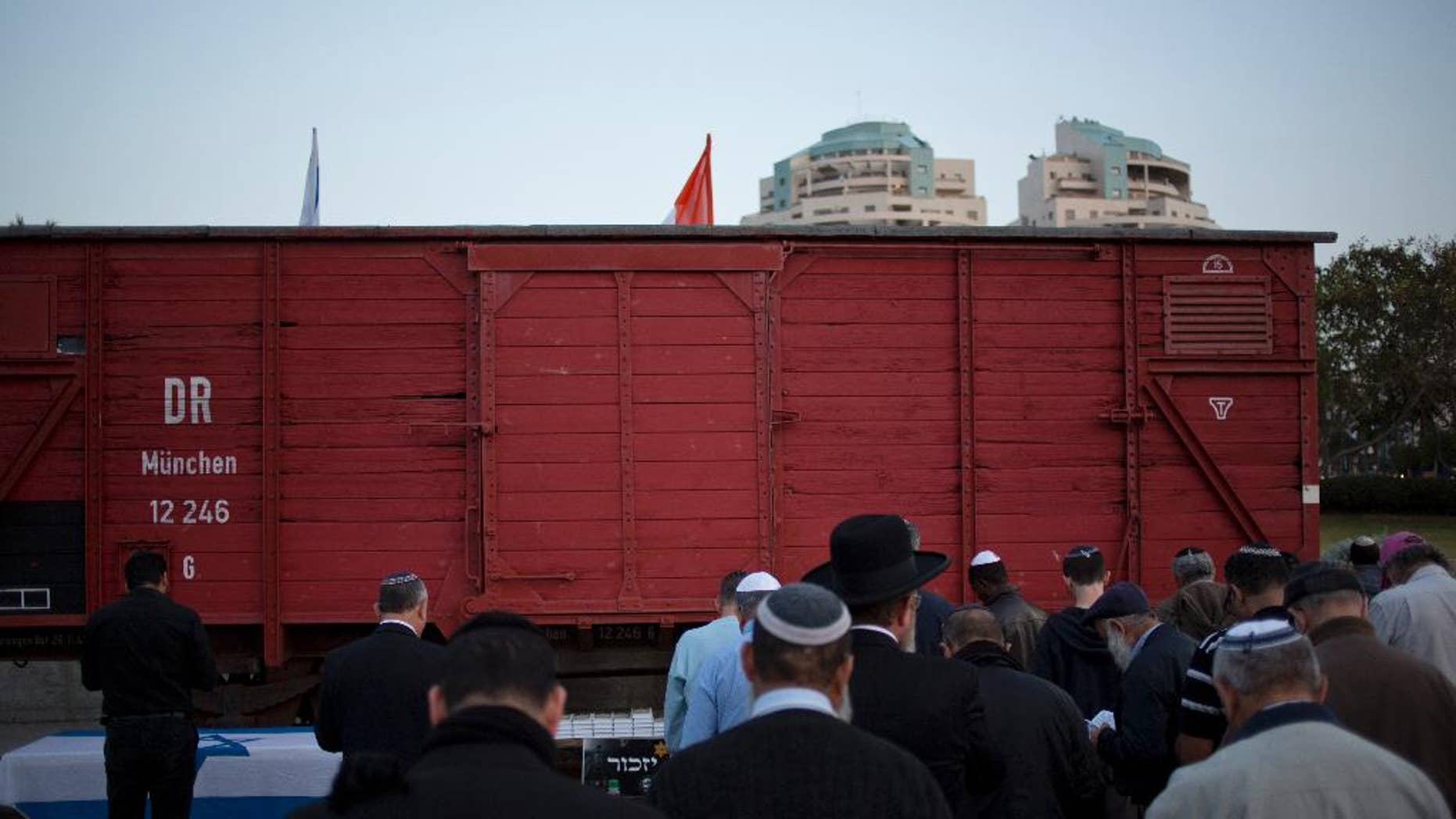 FILE -- People pray next to a wagon from WWII on display on the eve of Holocaust Remembrance Day in Netanya, Israel.