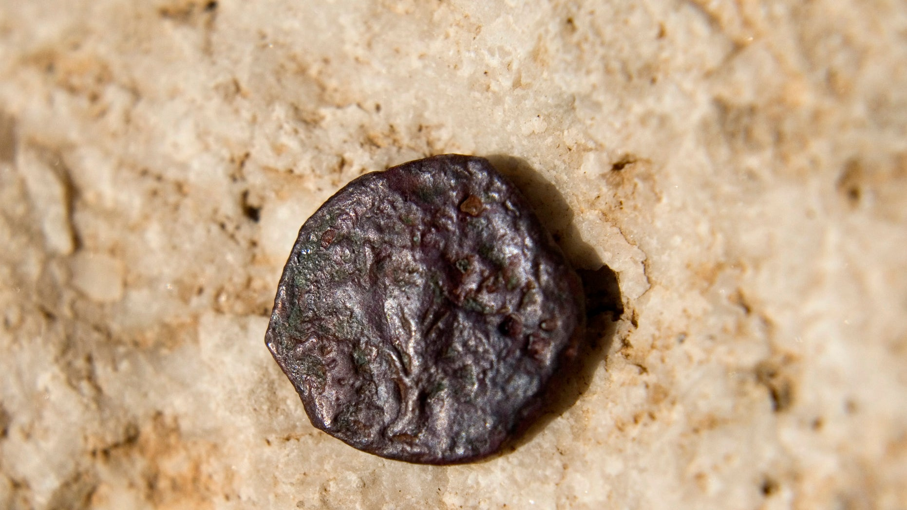 Nov. 23, 2011: An ancient coin, one of 17 discovered in an underground part of the Western Wall, the holiest site where Jews can pray, is seen in a presentation of archeological excavations in Jerusalem's Old City.