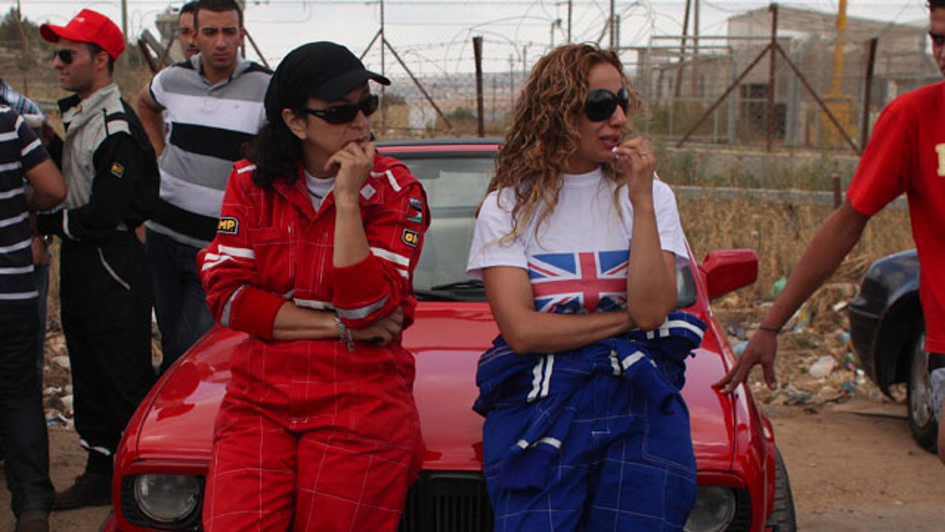 In this photo taken Friday, June 25, 2010, Palestinian Suna Awedia, center left, and Samia Khoury, center right, race car drivers, await their turns to race in the West Bank town of Ramallah. Palestinian women are speeding into record books by participating in their first all-female car racing team, the Speed Sisters. Along the way, they're crashing through another gender barrier in this conservative Muslim society.