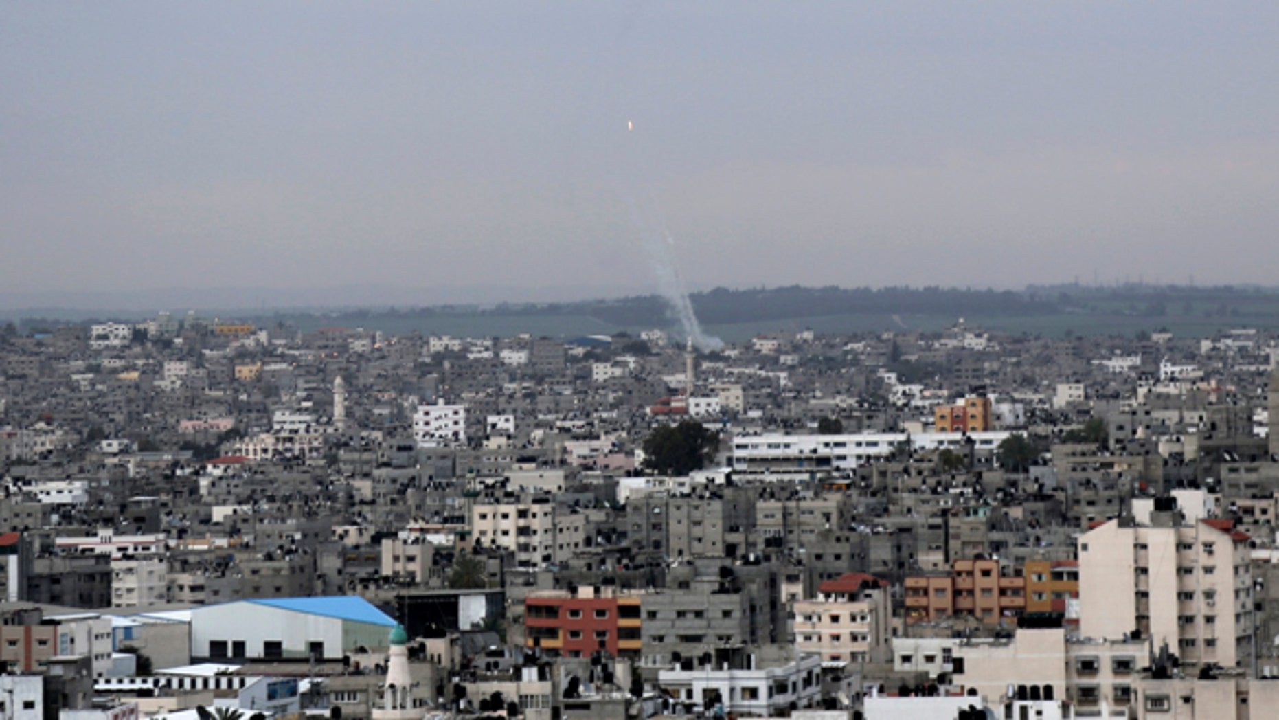 March 12, 2014: A trail of smoke from rockets fired by Palestinian militants from Gaza toward Israel is seen above Gaza City.
