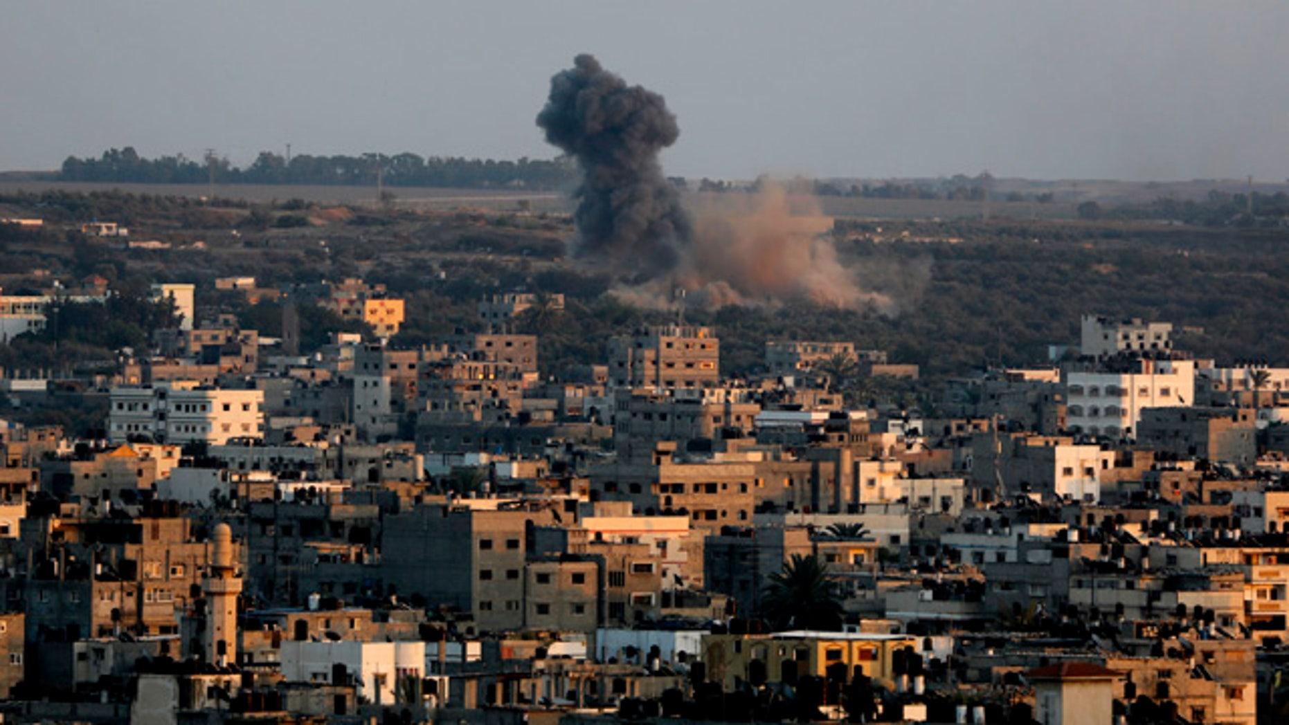 August 19, 2014: Smoke and dust rise after an Israeli strike hits Gaza City in the northern Gaza Strip. (AP Photo/Adel Hana)