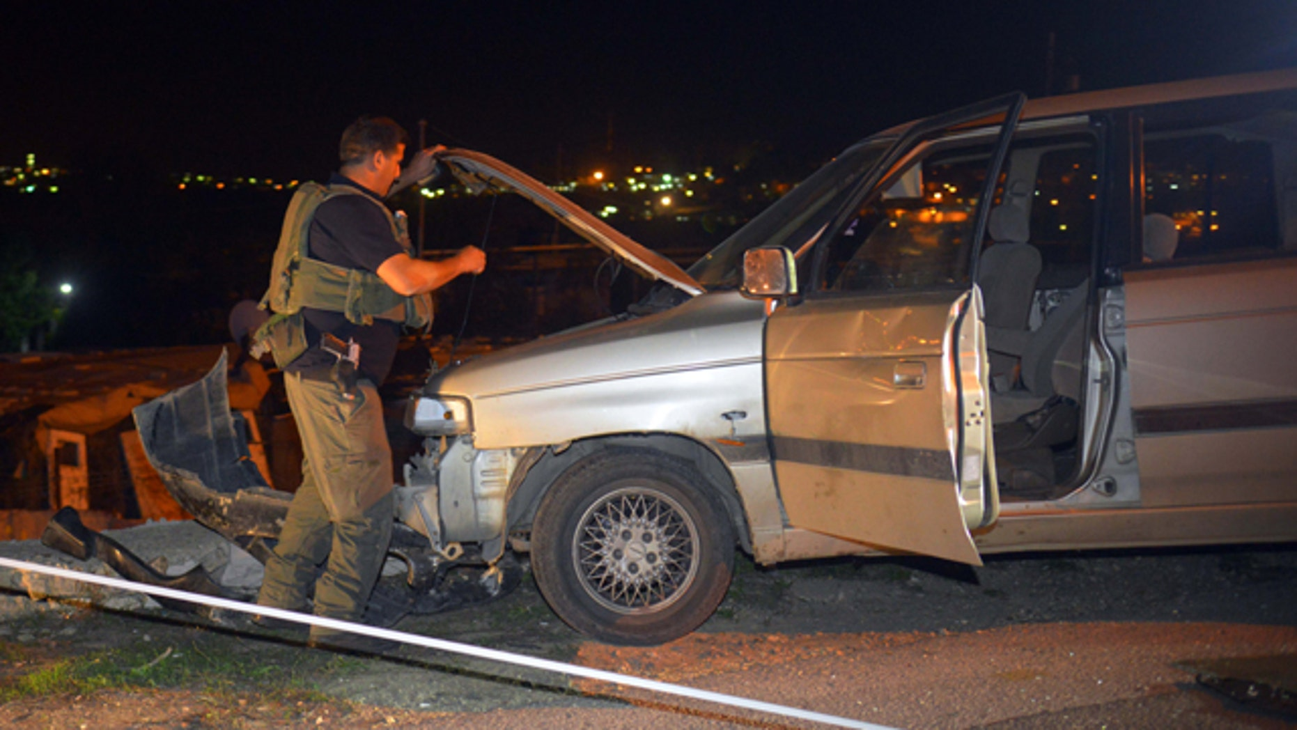 November 10, 2014: An Israeli soldier inspects a vehicle at the scene of an attack near the West Bank Jewish settlement of Alon Shvut. (AP Photo/Mahmoud Illean)