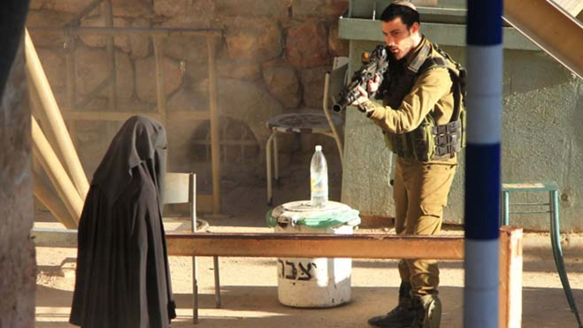 Sept. 22, 2015: An Israeli soldier aims at a Palestinian woman at a checkpoint in the West Bank city of Hebron.