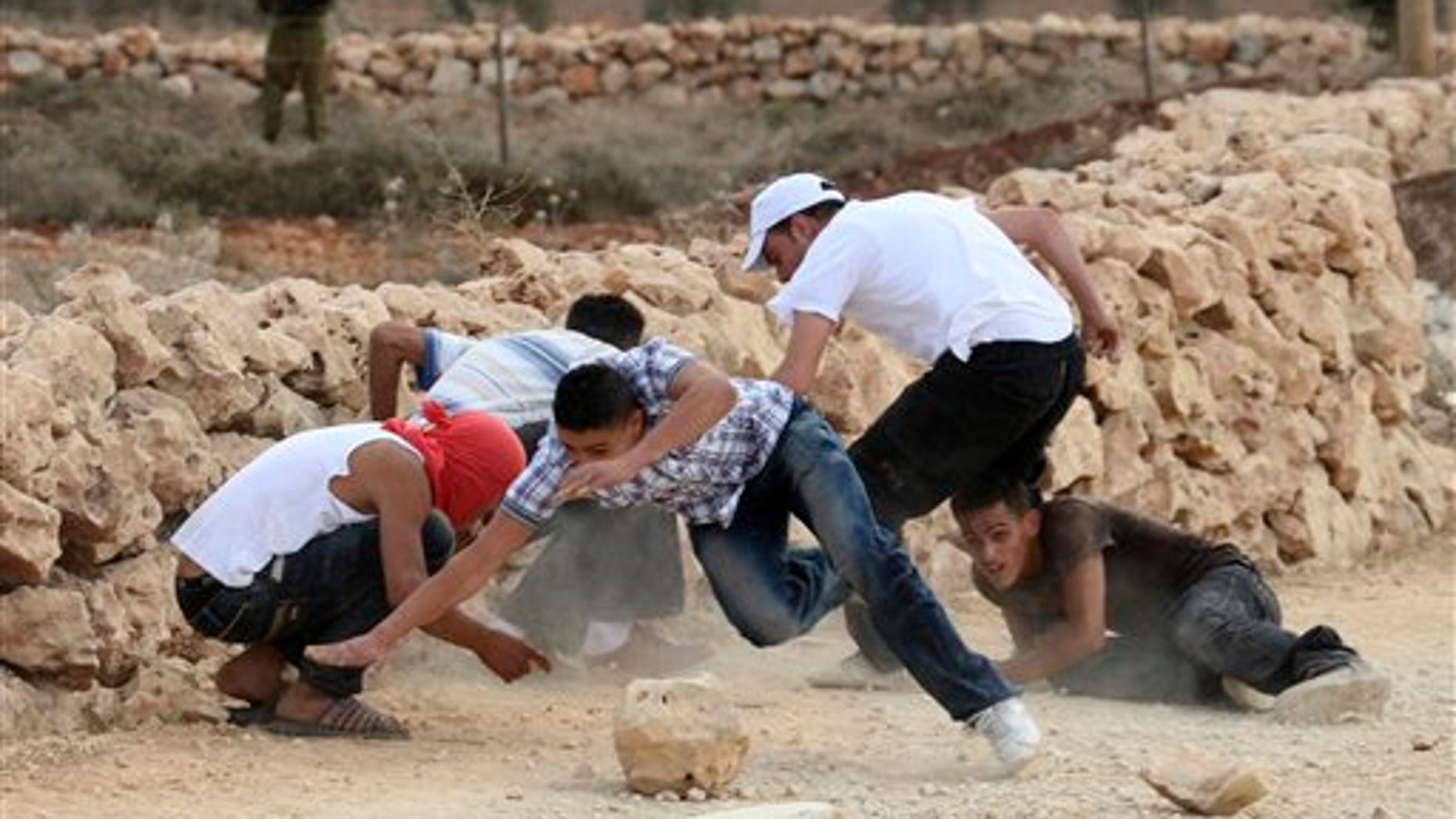 September 23: Palestinians scramble for cover during a clash with Israeli forces in the village of Qusra, south of Nablus, in the West Bank.