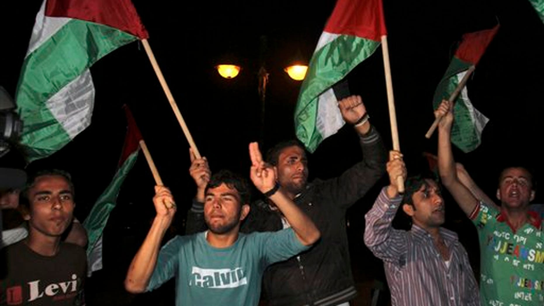 April 27: Palestinians wave flags and chant slogans in support of a reconciliation between the rival Fatah and Hamas movements, in Gaza City. Palestinians have reached initial agreement on reuniting their rival governments in the West Bank and Gaza, officials from both sides said Wednesday, a step that would remove a main obstacle in the way of peace efforts with Israel. (AP)