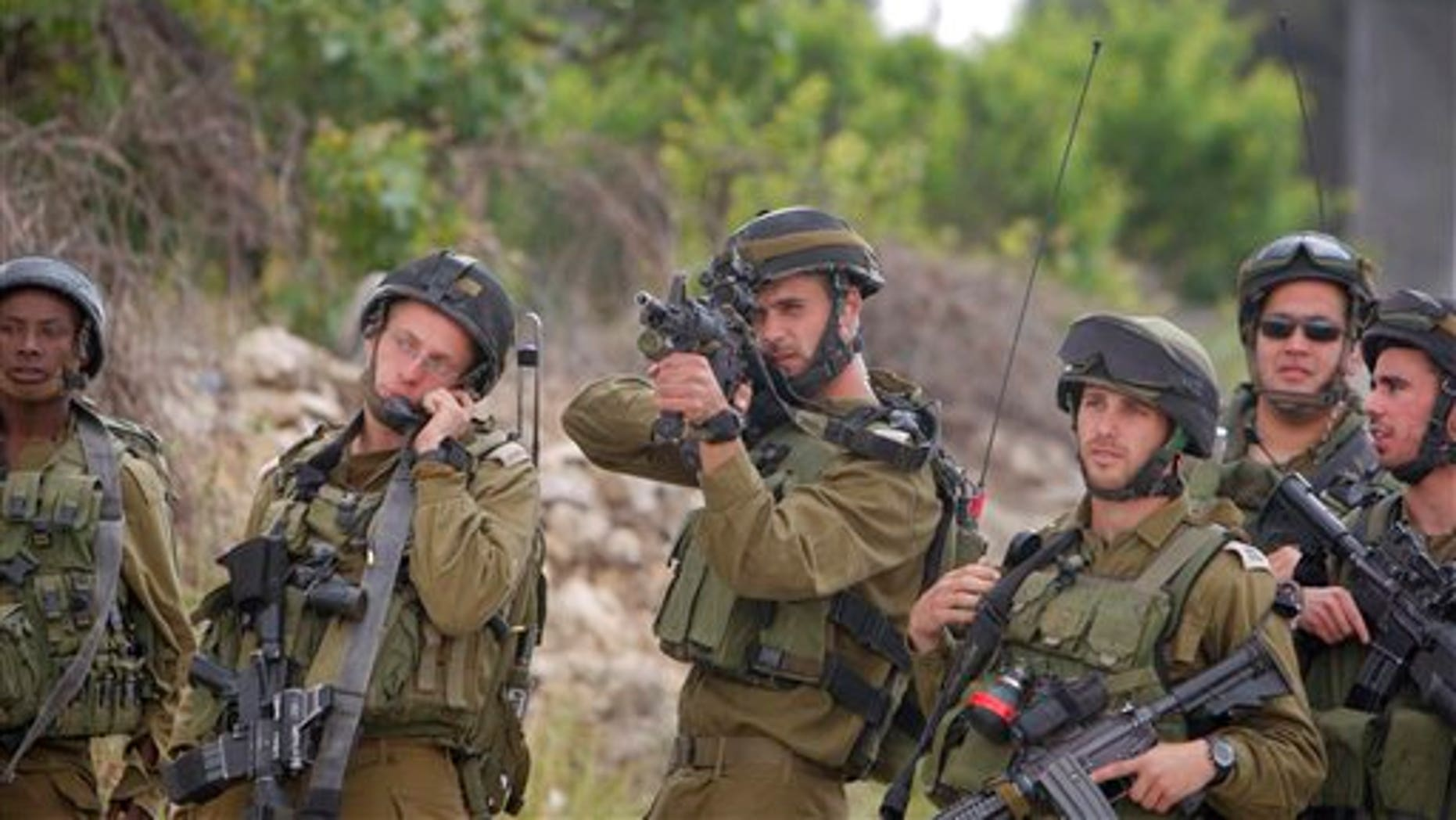 "May 15: Israeli soldiers take positions as  Palestinian youths, not seen, hurl stones during clashes at the Al-Roub refugee camp near the West Bank city of Hebron. The clashes erupted following a demonstration to mark the 63rd anniversary of ""Naqba"", Arabic for ""Catastrophe"", the term used to mark the events leading to Israel's founding in 1948. (AP)"