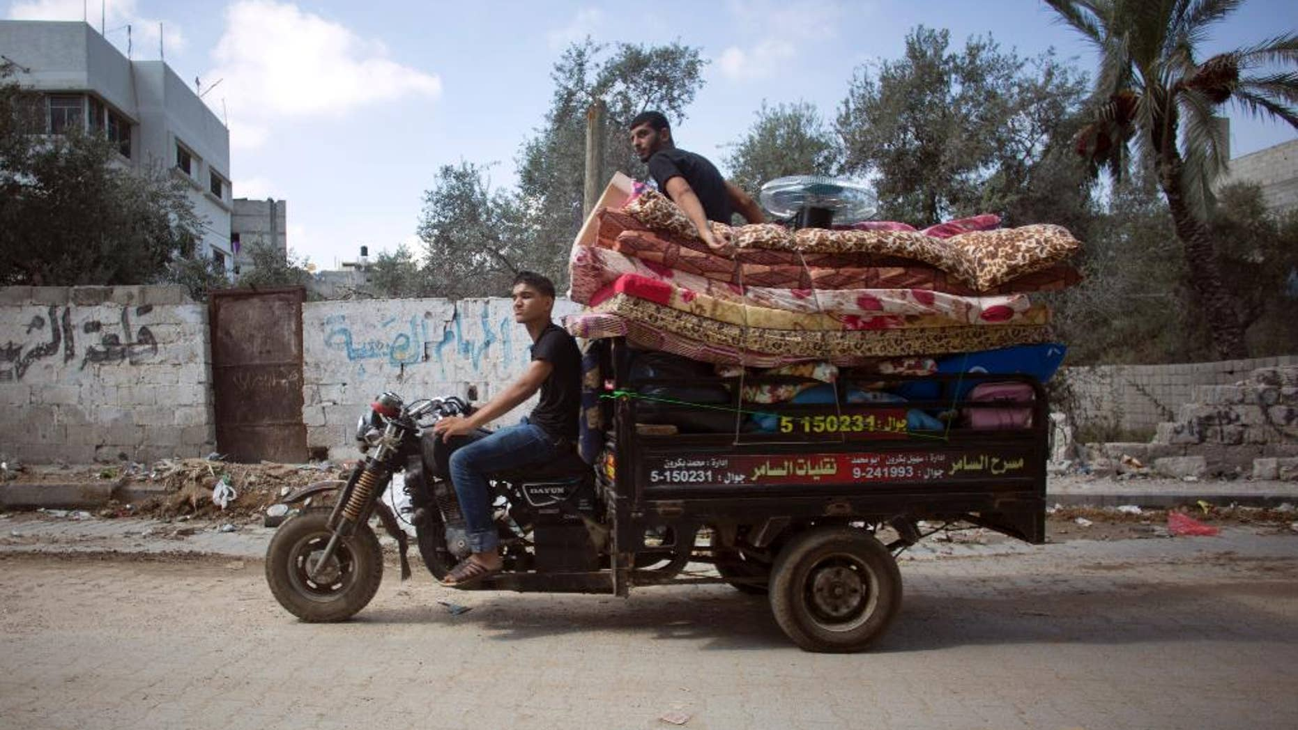 Palestinians with their belongings drive a motorbike back to their house in Gaza City's Shijaiyah neighborhood, Wednesday, Aug. 27, 2014. (AP Photo/Khalil Hamra)