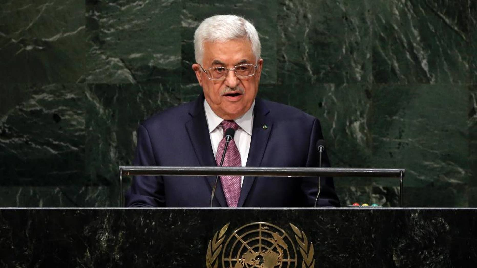 FILE - In this Friday, Sept. 26, 2014, file photo, Palestinian President Mahmoud Abbas addresses the 69th session of the United Nations General Assembly at U.N. headquarters. The U.N. has accepted Palestine's request join the International Criminal Court, setting April 1 as the starting date and clearing the way for potential war crimes investigations of Israel over its settlement building on occupied lands and a 2014 war in Gaza that killed hundreds of civilians.  (AP Photo/Richard Drew, File)