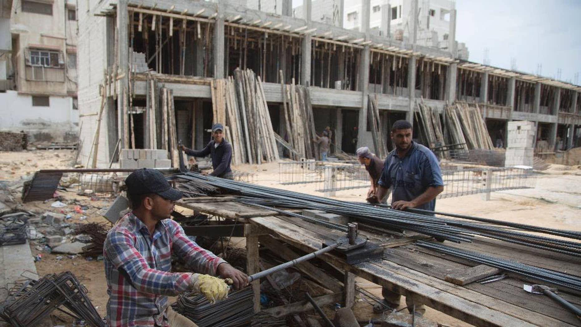 Palestinian construction laborers work on a U.N. school in the Gaza Strip, Saturday, Oct. 11, 2014. After the Gaza war, the U.N. brokered a deal with Israel and the Palestinian government under which Israel is to allow imports of construction materials for the private sector. On the Gaza side, the shipments are to be tracked by U.N. and Palestinian officials. (AP Photo/Khalil Hamra)