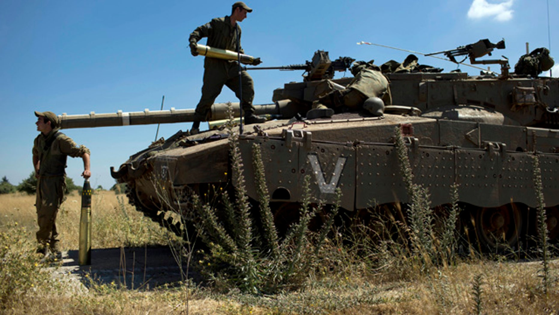 June 22, 2014: Israeli soldiers load shells in their tank following the first death on the Israeli side of the Golan since the Syrian civil war erupted more than three years ago, near the Israeli village of Alonei Habashan, in the area of Tel Hazeka, close to the Quneitra border crossing in the Israeli-controlled Golan Heights. (AP Photo/Oded Balilty)