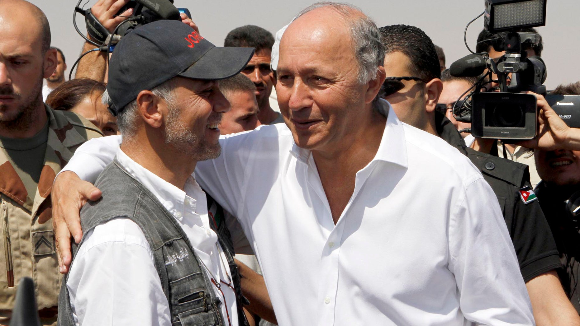French Foreign Minister Laurent Fabius, right,  greets an official from the Jordan Hashemite Charity Organization during his visit to the Zaatari Syrian refugee camp in Mafraq, Jordan, Thursday,  Aug. 16,  2012. Fabius is on a three-day visit to countries neighboring Syria. (AP Photo/Raad Adayleh)