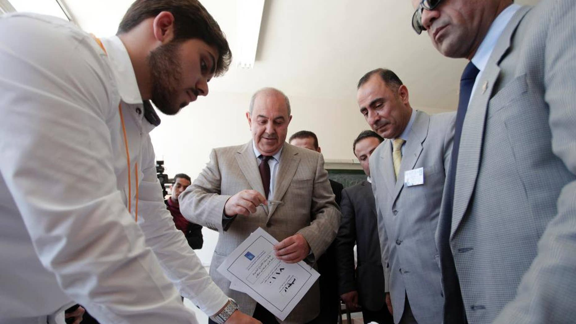"""Ayad Allawi, the leader of Iraq's main Sunni-backed Iraqiya bloc and former Prime Minister, center, arrives at a polling station as his identity is checked by one of the voting watchers, for the Iraqi parliamentary election, in Amman, Jordan, Sunday, April 27, 2014. After voting Allawi expressed his views on the election, """"really this is a shameful kind of elections, and I can categorize it by an election which is not worthy, not up to the standards of the Iraqi people, but this is the only way for change in Iraq, and I call upon all Iraqis to go to the ballot boxes to cast their votes to change the current situation,""""Allawi said.  (AP Photo/Mohammad Hannon)"""