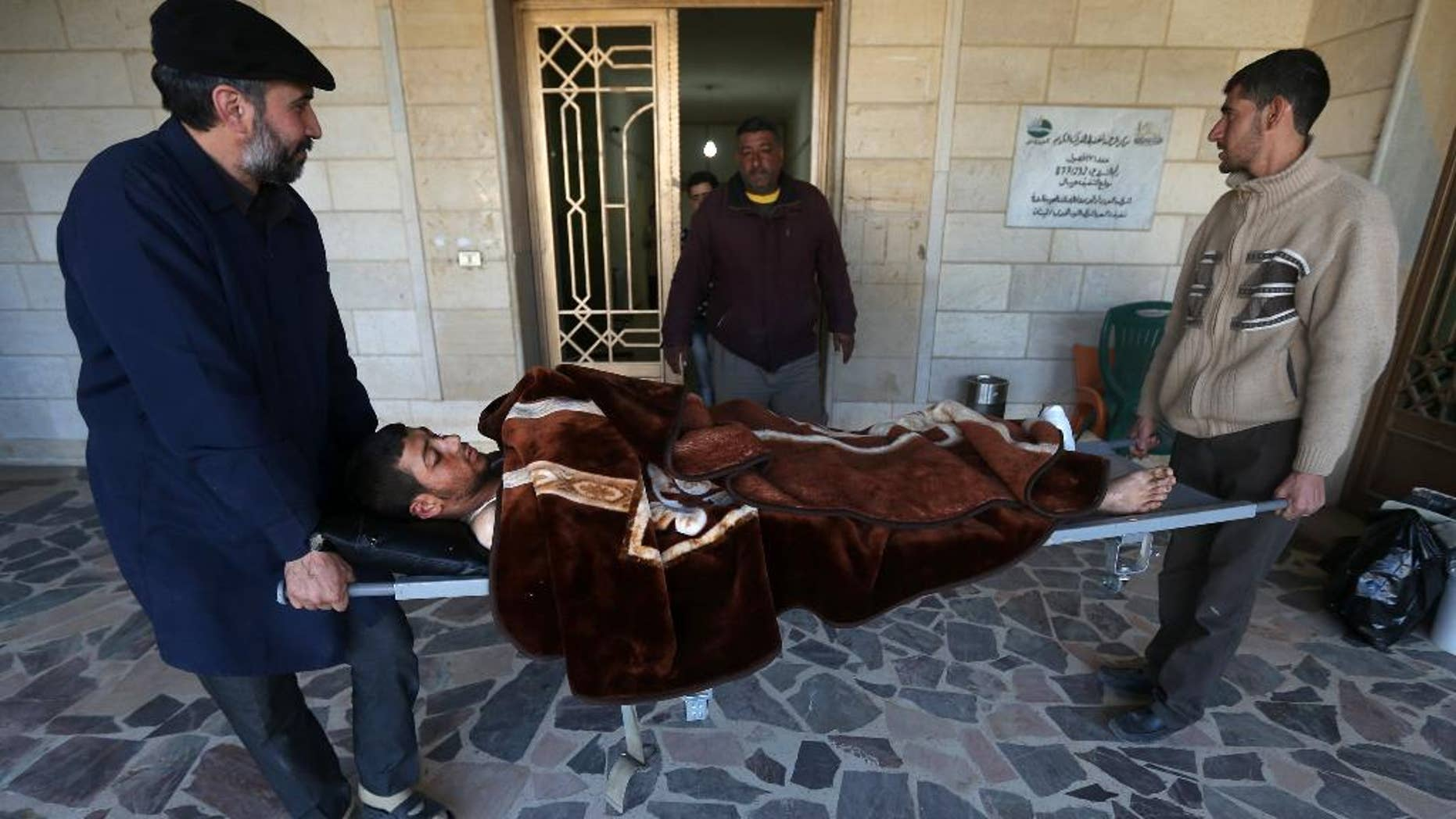 In this picture taken on Wednesday, March 5, 2014, a Lebanese nurse, left, and Syrian man, right, carry Adul-Karim, 18, a Syrian rebel who was injured during a battle against the Syrian government forces and Hezbollah fighters in Rima village near Yabroud, the last rebel stronghold in Syria's mountainous Qalamoun region, as they move him from a makeshift hospital to a rest house after he received his medical treatment, in the Lebanese-Syrian border town of Arsal, eastern Lebanon. Trucks of armed fighters rumble from this Lebanese Sunni town through the mountains to the front in Syria, where rebels are in a furious fight to keep a vital stronghold. At the same time, Lebanese Shiite fighters from a town not far away are also streaming in to join the battle _ but on the opposing side, backing Syrian government forces. The battle has effectively erased the border between the two countries and underlines how dangerously Lebanon is being sucked into its neighbor's civil war. (AP Photo/Hussein Malla)