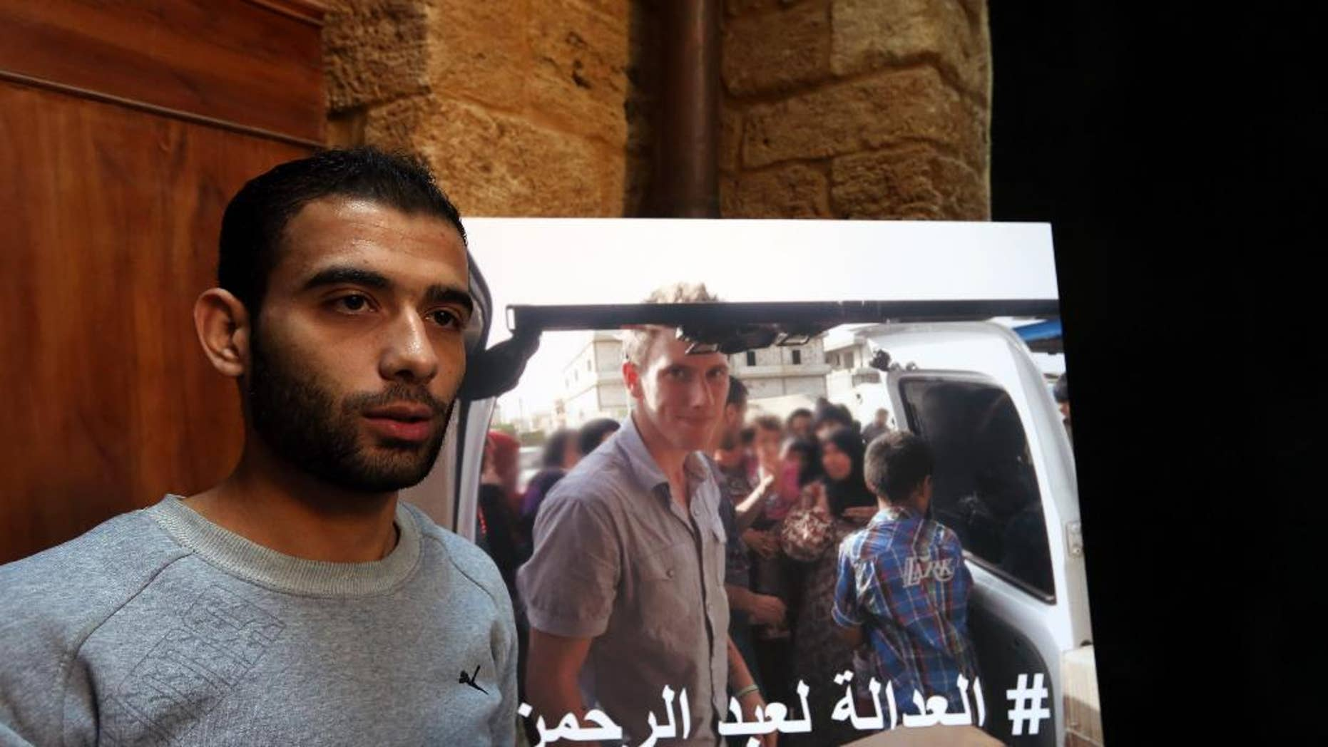 """Syrian refugee Amjad Moghrabi stands in front of a photograph of his colleague, American aid worker Peter Kassig, 26, who converted to Islam while in captivity and changed his name to Abdul-Rahman Kassig, during an interview with The Associated Press in the northern port city of Tripoli, Lebanon, Saturday, Nov. 8, 2014. Kassig was helping victims of the Syrian civil war when he was captured in Syria last year and threatened with beheading by the Islamic State group. Arabic  reads, """"Justice for Abdul-Rahman."""" (AP Photo/Bilal Hussein)"""