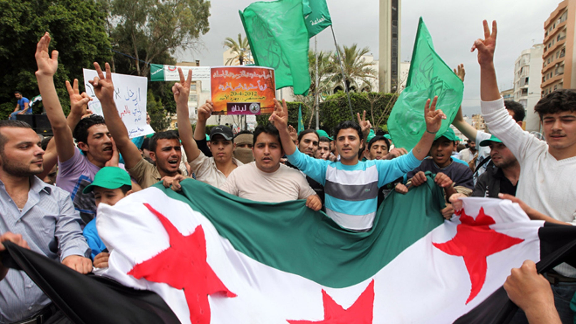April 20, 2012: Supporters of an Islamic group and Lebanon's Future Movement of former Prime Minister Saad Hariri, wave their party flags and a giant Syrian revolution flag, and shout slogans as they march during a demonstration against the Syrian regime and to show their solidarity with the Syrian people, after Friday prayers, in Beirut, Lebanon.