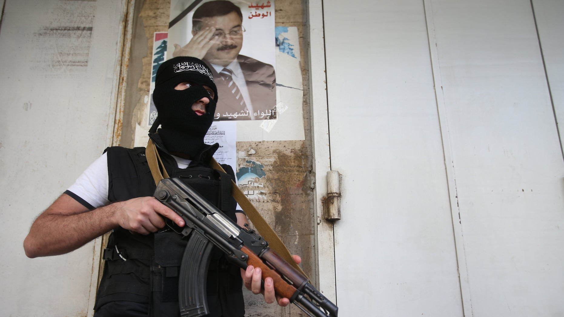 A masked Sunni gunman stands guard under a portrait of Brig. Gen. Wissam al-Hassan, who was assassinated on Friday by a car bomb, on a blocked street leading to a Shiite neighborhood after overnight clashes that erupted between Sunni and Shiite gunmen in Beirut, Lebanon, Monday Oct. 22, 2012. Lebanese security officials say overnight clashes in Beirut between Sunni and Shiite gunmen have wounded several people. The officials say troops managed to separate the gunmen and calm returned Monday morning to the two neighborhoods in the capital where fighting had erupted. (AP Photo/Hussein Malla)