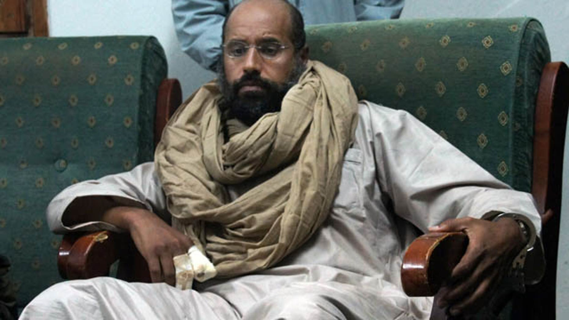 FILE - In this Saturday, Nov. 19, 2011 file photo, Seif al-Islam is seen after his capture in the custody of revolutionary fighters in Zintan. (AP Photo/Ammar El-Darwish, File)