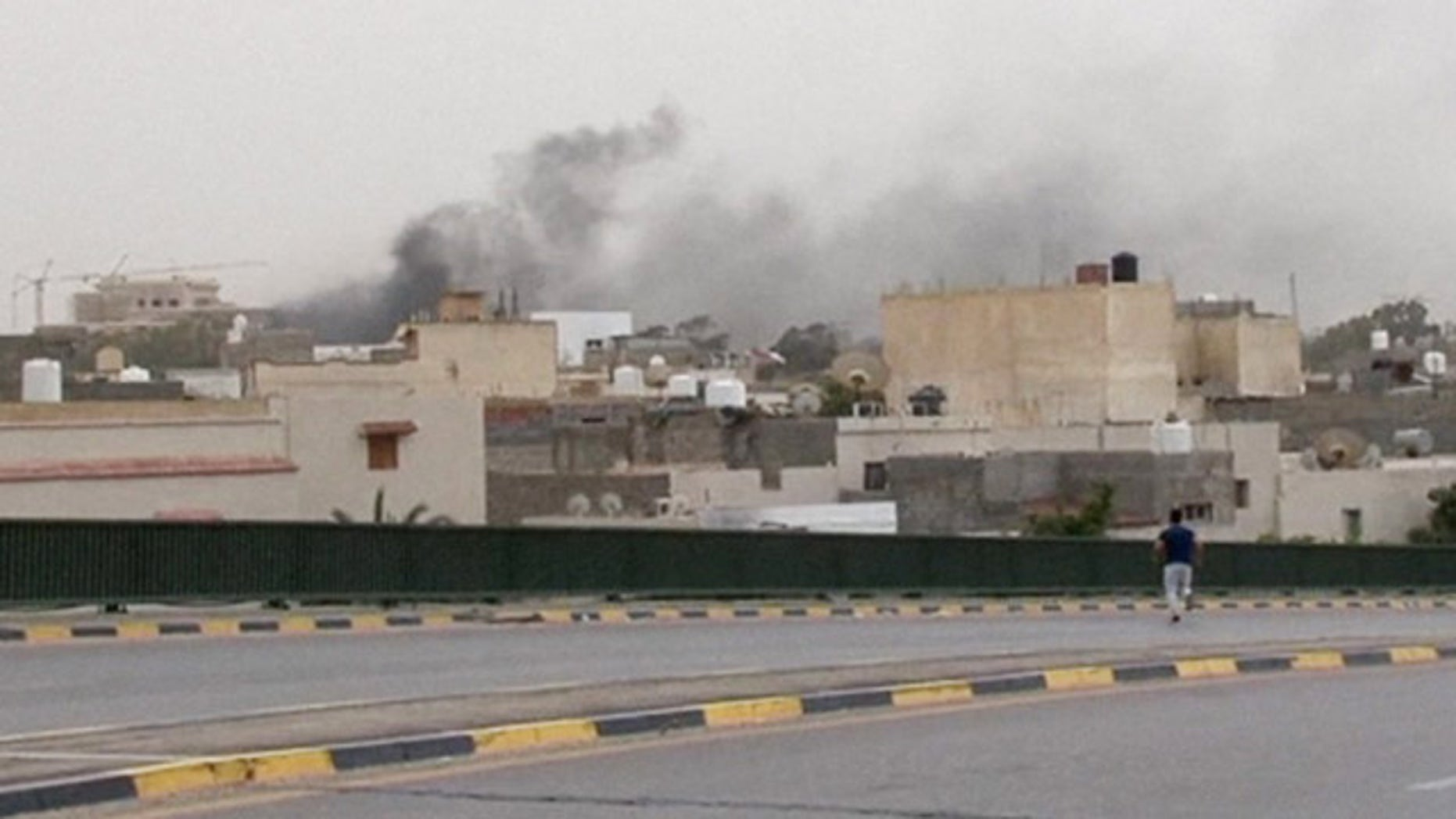 May 18, 2014: In this image made from video provided by the Libyan national army via AP Television, smoke rises over the parliament area after troops of Gen. Khalifa Hifter targeted Islamist lawmakers and officials at the parliament in Tripoli. (AP Photo/Libyan national army)