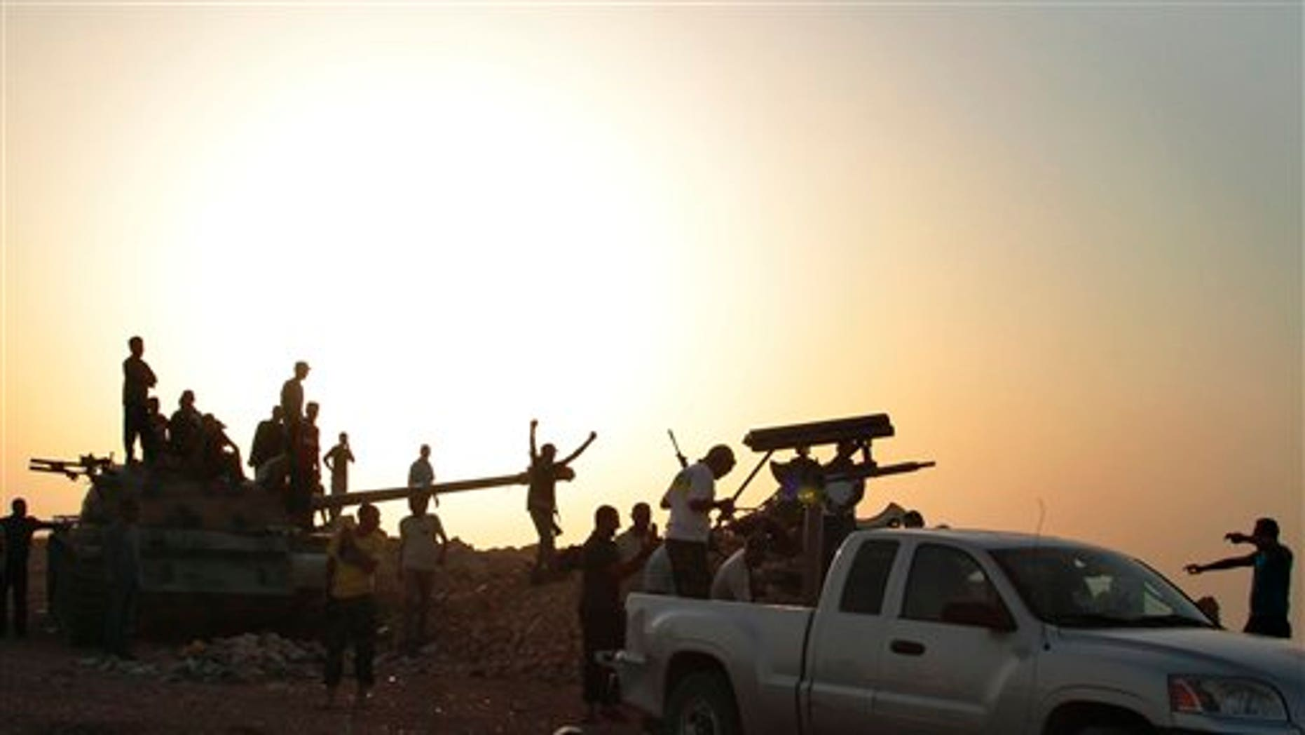 July 14: Libyan rebels gather around a captured tank in Kabaw, western Libya.