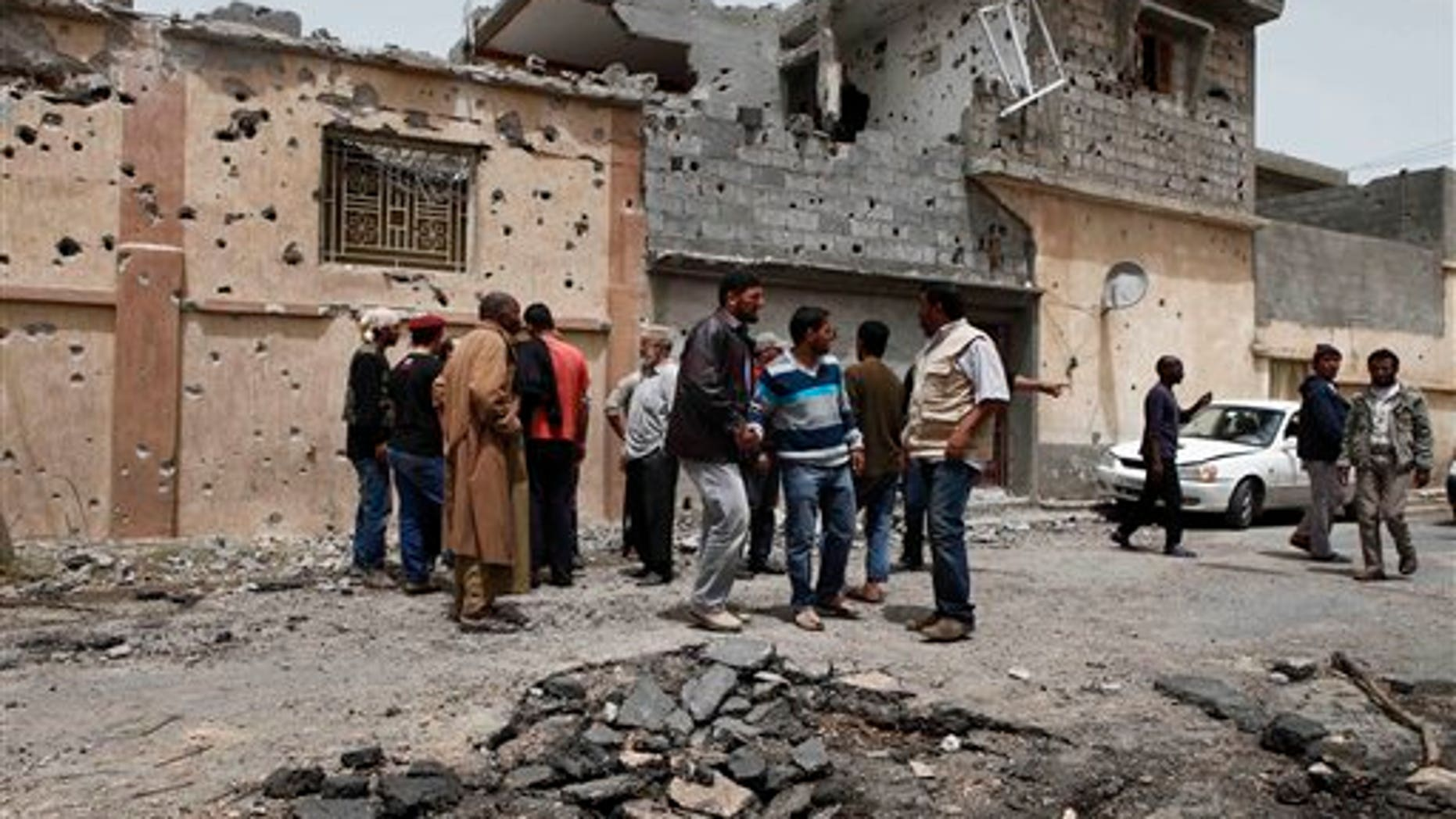 April 25: Neighbors examine the damage to a house which was struck by a shell in Misrata. Qaddafi's troops on the outskirts of Misrata unleashed more shells into the city Monday, hitting a residential area and killing 10 people, including five members of one family, according to a doctor in Misrata. (AP)