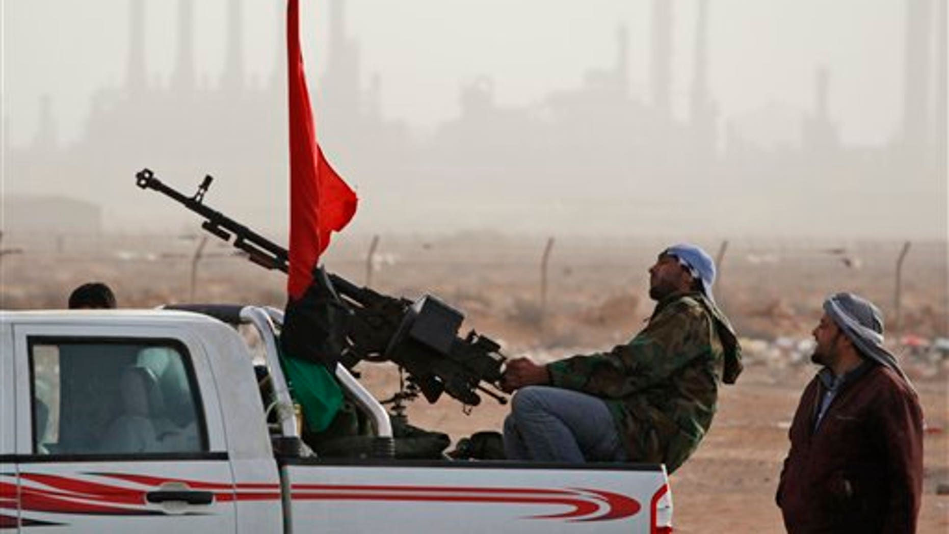March 5: Libyan rebels who are part of the forces against Libyan leader Muammar al-Qaddafi guard outside the refinery after their victory in fighting against troops loyal to Qaddafi in the oil town of Ras Lanuf, eastern Libya.