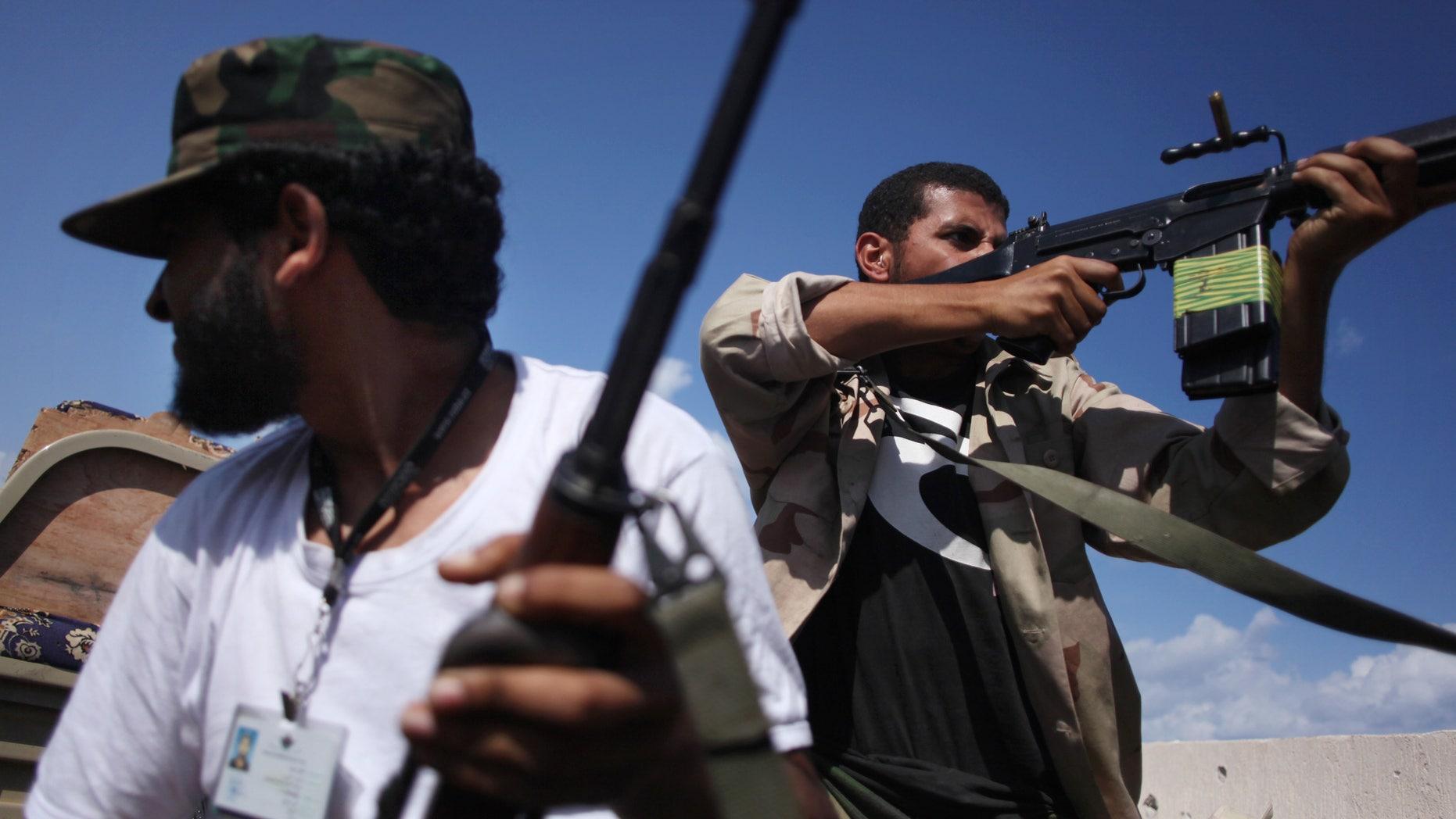 Oct. 18, 201:  Revolutionary fighters fire at Qaddafi loyalists in downtown Sirte, Libya.