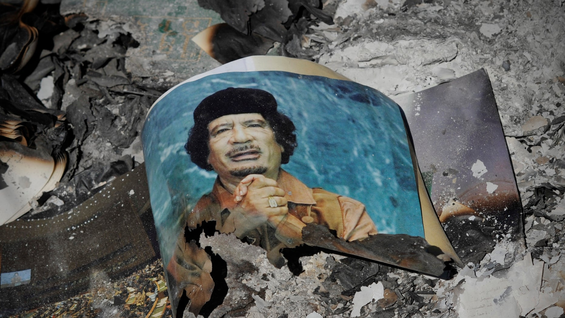 A picture of Libya's ousted leader Muammar Qaddafi is seen in the ashes in downtown Sirte, Libya, Wednesday, Oct. 12, 2011.