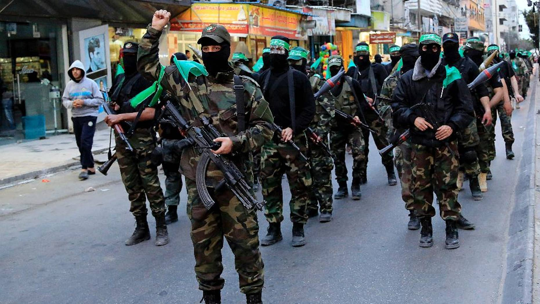 FILE - In this Monday, March 23, 2015, file photo, Palestinian masked militants of Izzedine al-Qassam Brigades, a military wing of Hamas, take part in a parade to mark the 11th anniversary of the Israeli assassination of Hamas spiritual leader Sheikh Ahmad Yassin in Gaza, in the northern Gaza Strip. Egypt's state news agency is reporting a court has overturned a decision naming Hamas a terrorist organization. The MENA news agency reported Saturday that the Urgent Matters Appeals Court made the decision. They cited a lack of jurisdiction for overturning the early court's ruling. (AP Photo/Adel Hana, File)