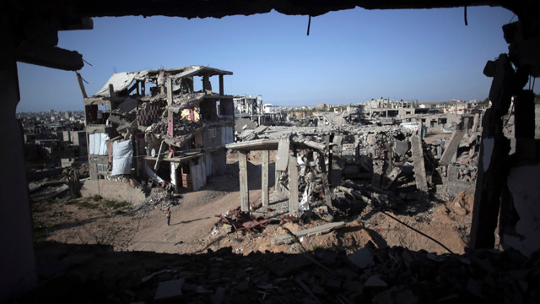 File - In this March 30, 2015 file photo, a Palestinian girl walks next to destroyed houses, in the Shijaiyah neighborhood of Gaza City. (AP Photo/Khalil Hamra, File)