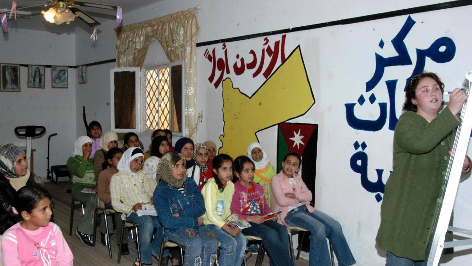 """This Nov. 16, 2006 photo provided by the Peace Corps, Andrea Girard from Coulterville, CA., teaches English at an all girls school in Jordan. The Peace Corps said Saturday, March 7, 2015, it is temporarily suspending its program in Jordan because of the """"regional environment,"""" highlighting growing security concerns among some foreigners after Jordan raised its profile in the battle against Islamic State militants. The Peace Corps said 37 volunteers had been working with local communities on youth development, and that all volunteers have left Jordan.  (AP Photo/Peace Corps)"""