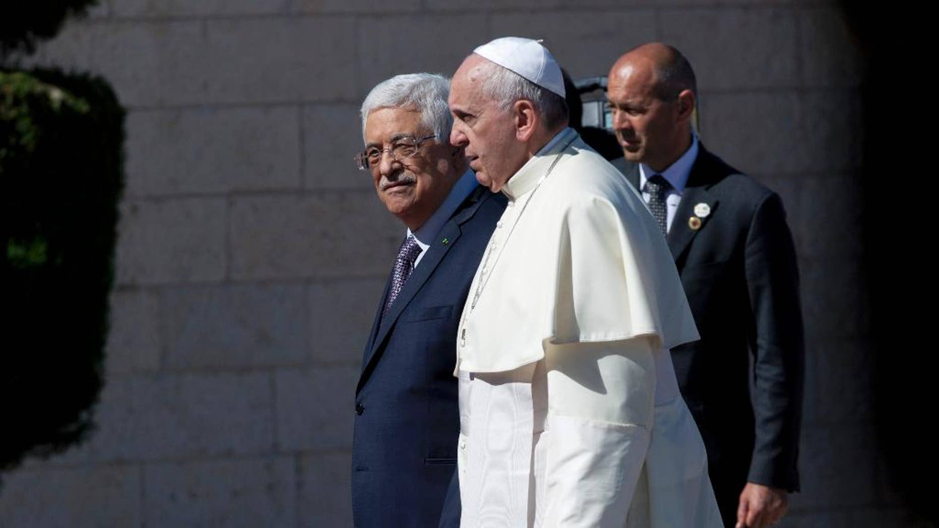 Palestinian President Mahmoud Abbas, left, receives Pope Francis upon his arrival at the Palestinian Authority headquarters in the West Bank city of Bethlehem on Sunday, May 25, 2014. Francis landed Sunday in the West Bank town of Bethlehem in a symbolic nod to Palestinian aspirations for their own state as he began a busy second day of his Mideast pilgrimage. (AP Photo/Nasser Nasser)