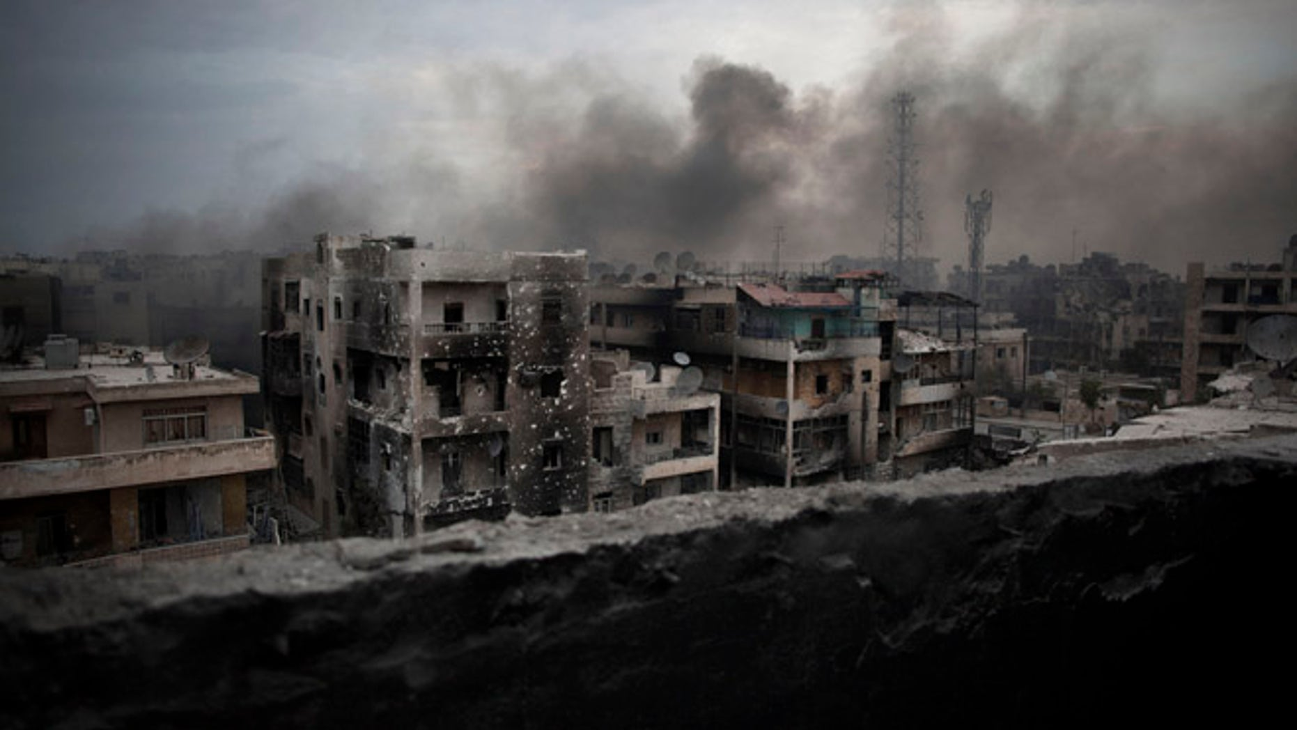 FILE - In this Tuesday, Oct. 2, 2012 file photo, smoke rises over Saif Al Dawla district, in Aleppo, Syria. Residents in the rebel-held districts of Aleppo have a reprieve from the incessant bombings by Syrian government warplanes and the promise of an end to the crippling siege that has left produce stalls bare. (AP Photo/ Manu Brabo, File)
