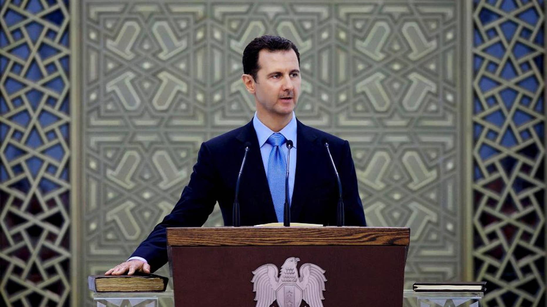 FILE - In this Wednesday, July 16, 2014 file photo released by the Syrian official news agency SANA, Syria's President Bashar Assad is sworn for his third, seven-year term, in Damascus, Syria. Assad said in remarks published Wednesday that U.S.-led airstrikes targeting Islamic State group militants in his country are neither serious nor efficient, claiming they have failed to produce any tangible results. (AP Photo/SANA, File)