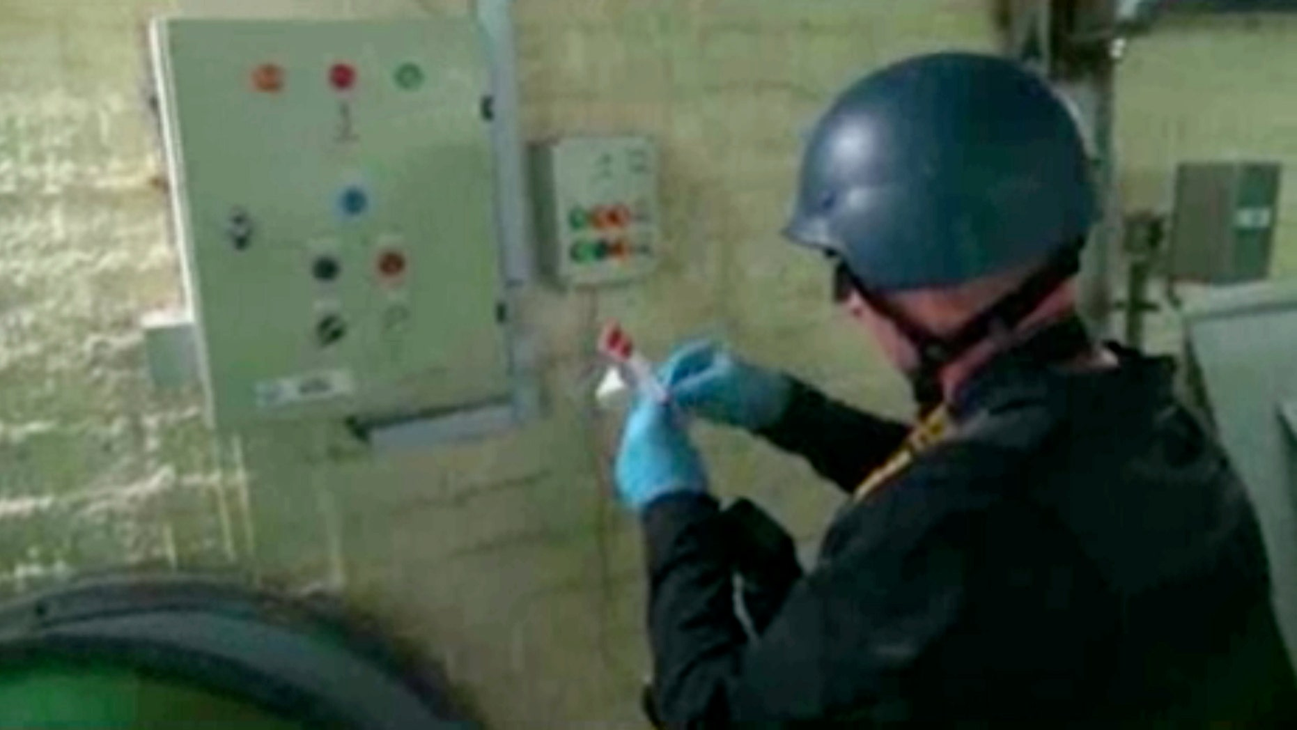 Oct. 8, 2013 - FILE image made from video broadcast on Syrian State Television shows a chemical weapons expert taking samples at a chemical weapons plant at an unknown location in Syria. The dismantling of Syria's chemical weapons stockpile is under way, but the mission faces multiple challenges.