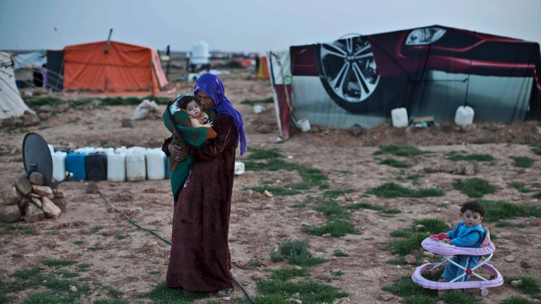 FILE - In this Sunday, March 8, 2015 file photo, Syrian refugee Rifaa Ahmad, 50, cuddles her granddaughter at an informal tented settlement near the Syrian border, on the outskirts of Mafraq, Jordan. Kuwait opened an international donors' conference for Syria on Tuesday, March 31, 2015 with a pledge of $500 million in humanitarian aid as the United Nations issued its largest yet appeal for $8.4 billion in commitments this year for the war-ravaged country.(AP Photo/Muhammed Muheisen, File)