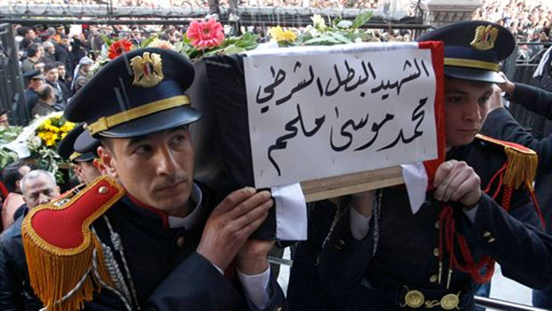 Jan. 7: Syrian police honor guards carry the coffin of one of 11 Syrian police officers who were killed in an explosion in the Midan neighborhood on Friday, during a mass funeral procession at Al-Hassan mosque, in Damascus, Syria.