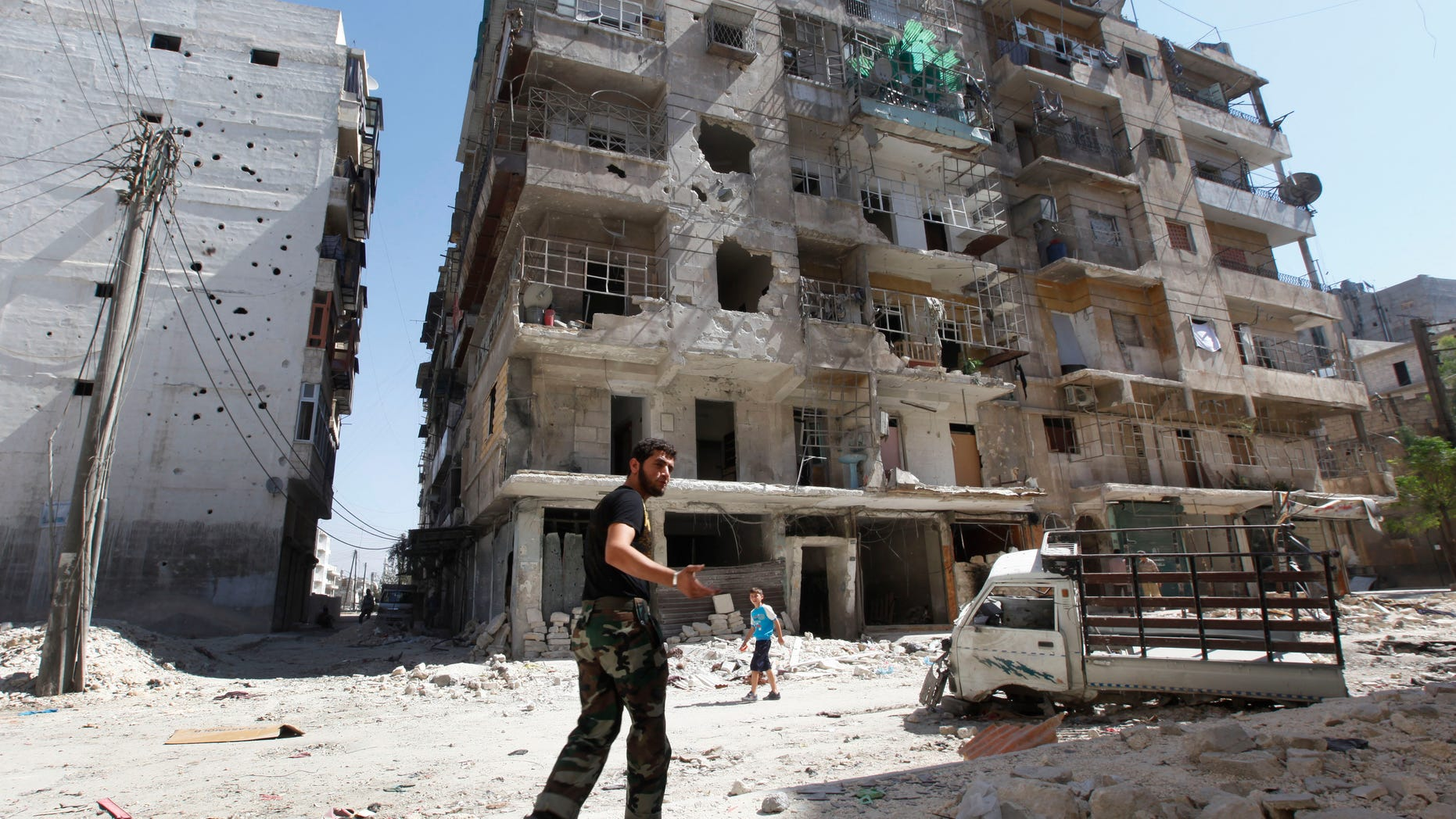 A Frre Syrian Army soldier, walks next of a destroyed building that was attacked by a Syrian government airstrike earlier in the day at al-Shaar neighborhood, in Aleppo city, Syria, Monday Sept. 24, 2012. Most of those fighting the regime of President Bashar Assad are ordinary Syrians and soldiers who have defected, having become fed up with the authoritarian government, analysts say. But increasingly, foreign fighters and those adhering to an extremist Islamist ideology are turning up on the front lines. (AP Photo/Hussein Malla)