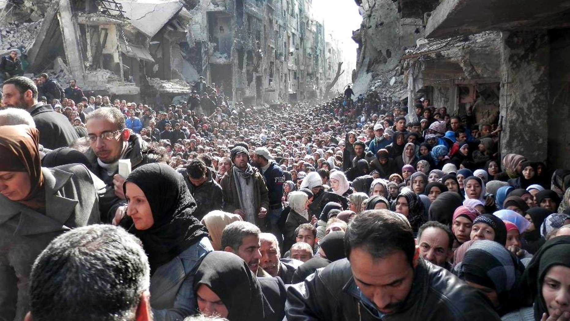 FILE - In this Jan. 31, 2014, file photo, released by the United Nations Relief and Works Agency for Palestine Refugees in the Near East (UNRWA), shows residents of the besieged Palestinian camp of Yarmouk, queuing to receive food supplies, in Damascus, Syria. UNRWA spokesman Christopher Gunness says the agency needs around $250 million to fund its cash program, which provides cash distributions for roughly half a million Palestinian refugees affected by the war in Syria. (AP Photo/UNRWA, File)