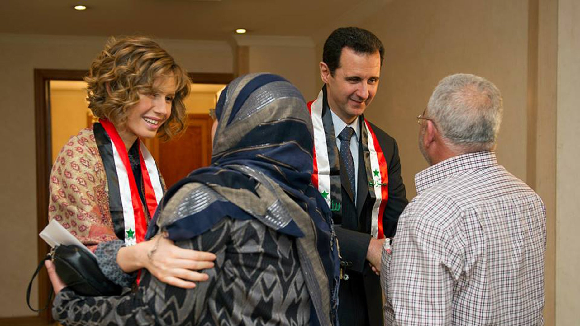 March 20, 2014: This photo posted on the official Facebook page of the Syrian Presidency, shows first lady Asma Assad, left background, and Syrian President Bashar Assad, right background, shaking hands with Syrian teachers in Damascus, Syria.