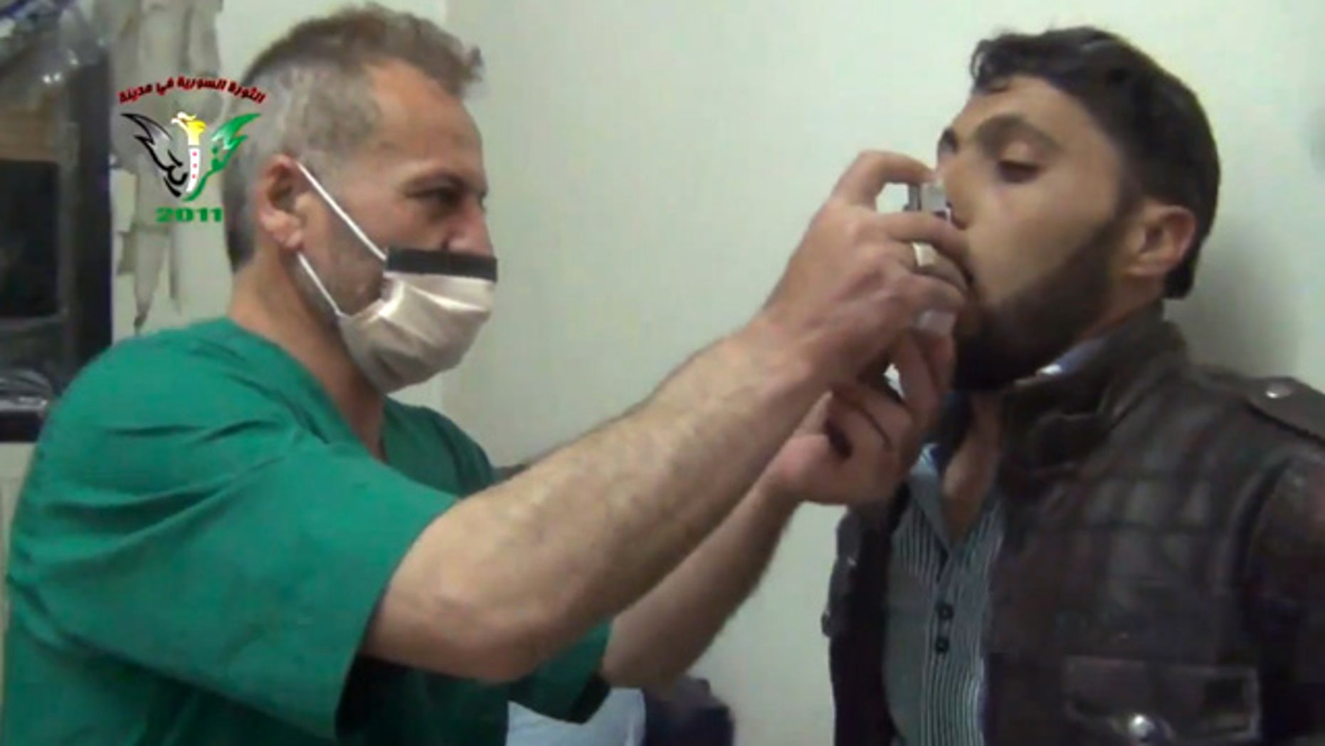 April 18, 2014: In this image taken from video obtained from the Shaam News Network, an anti-Bashar Assad activist group, which has been authenticated based on its contents and other AP reporting, a Syrian man is treated with an inhaler in Kfar Zeita, a rebel-held village in Hama province some 125 miles north of Damascus. (AP Photo/Shaam News Network)