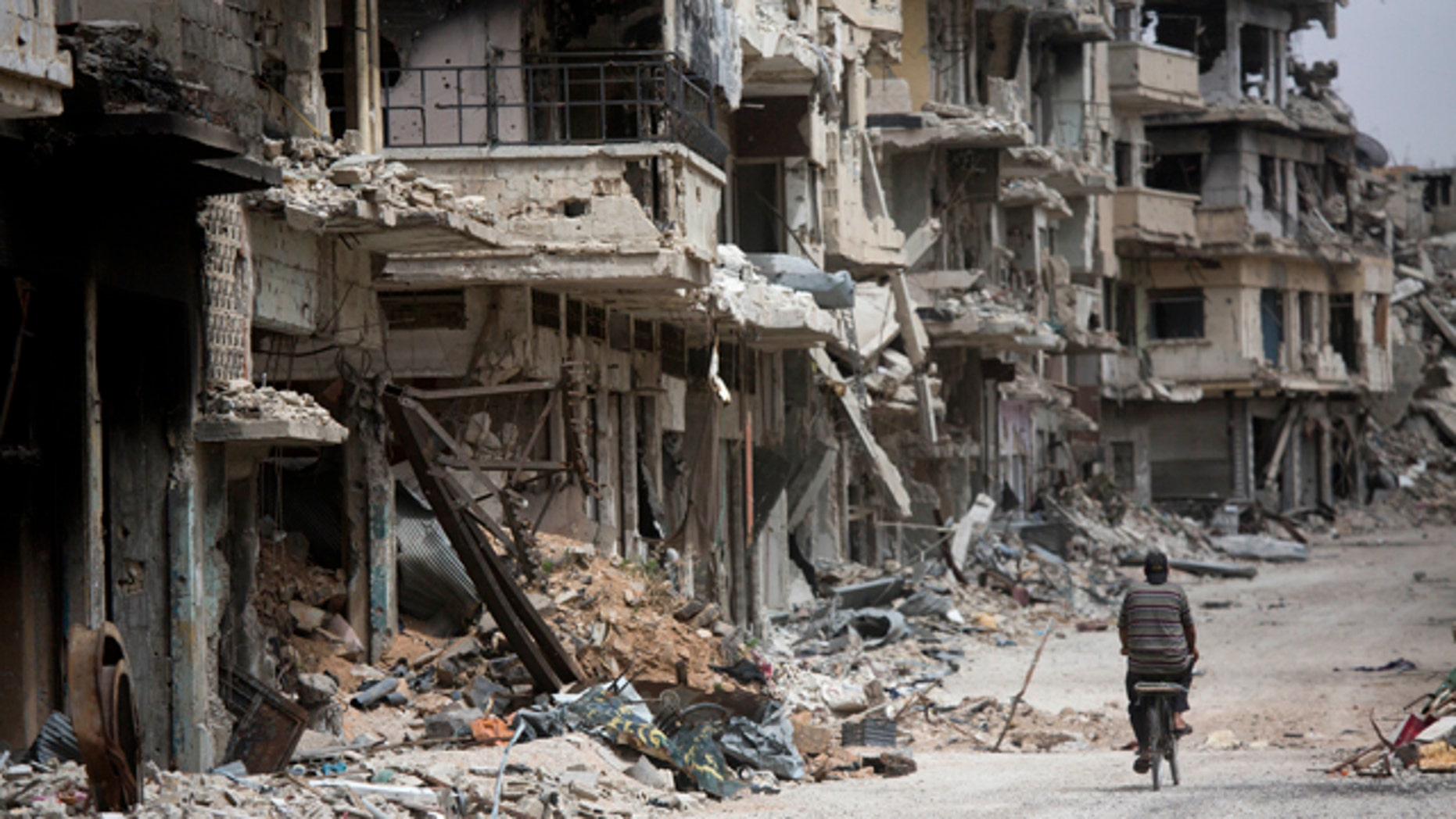 FILE - In this June 5, 2014, file photo, a man rides a bicycle  through a devastated part of Homs, Syria. (AP Photo/Dusan Vranic, File)