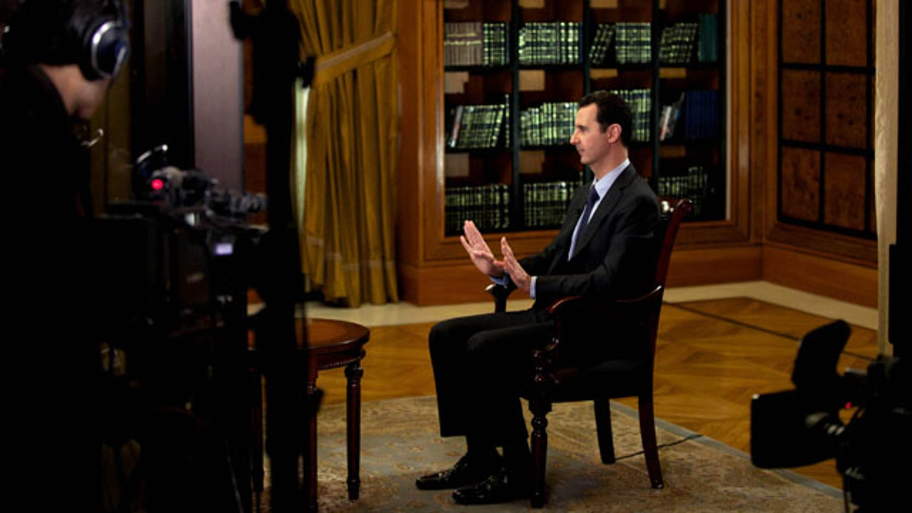 October 21, 2013: In this photo, which AP obtained from Syrian official news agency SANA and which has been authenticated based on its contents and other AP reporting, President Bashar Assad gestures as he speaks during an interview with Lebanon's Al-Mayadeen TV, at the presidential palace in Damascus, Syria, Monday. (AP Photo)
