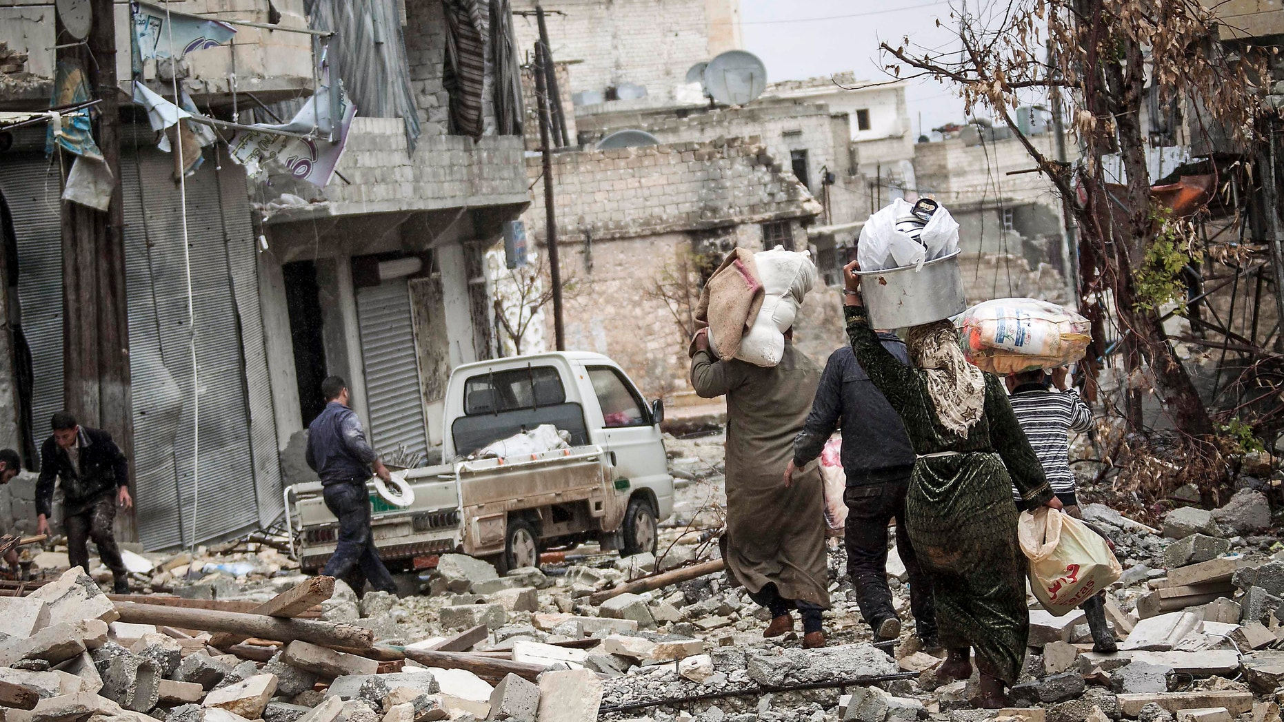 Dec. 11, 2012 - Syrian residents carry their belongings after their homes were damaged due to fighting between Free Syrian Army fighters and government forces in Aleppo, Syria.