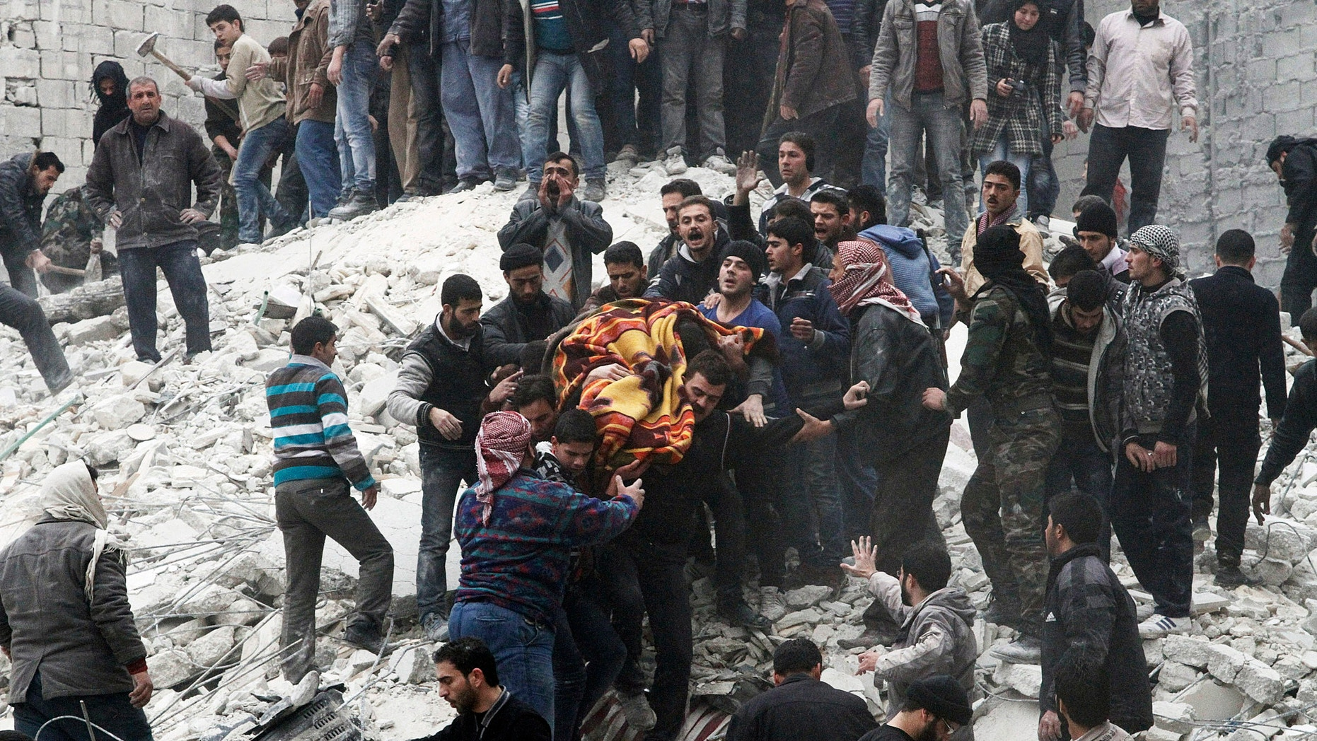 Feb. 3, 2013 - Syrian people carry a body after a government airstrike hit the neighborhood of Ansari, in Aleppo, Syria.