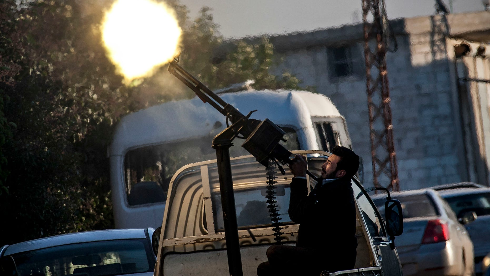Dec. 15, 2012: In this photo, A Free Syrian Army fighter fires a weapon during heavy clashes with government forces at a academy besieged by rebels north of Aleppo, Syria.
