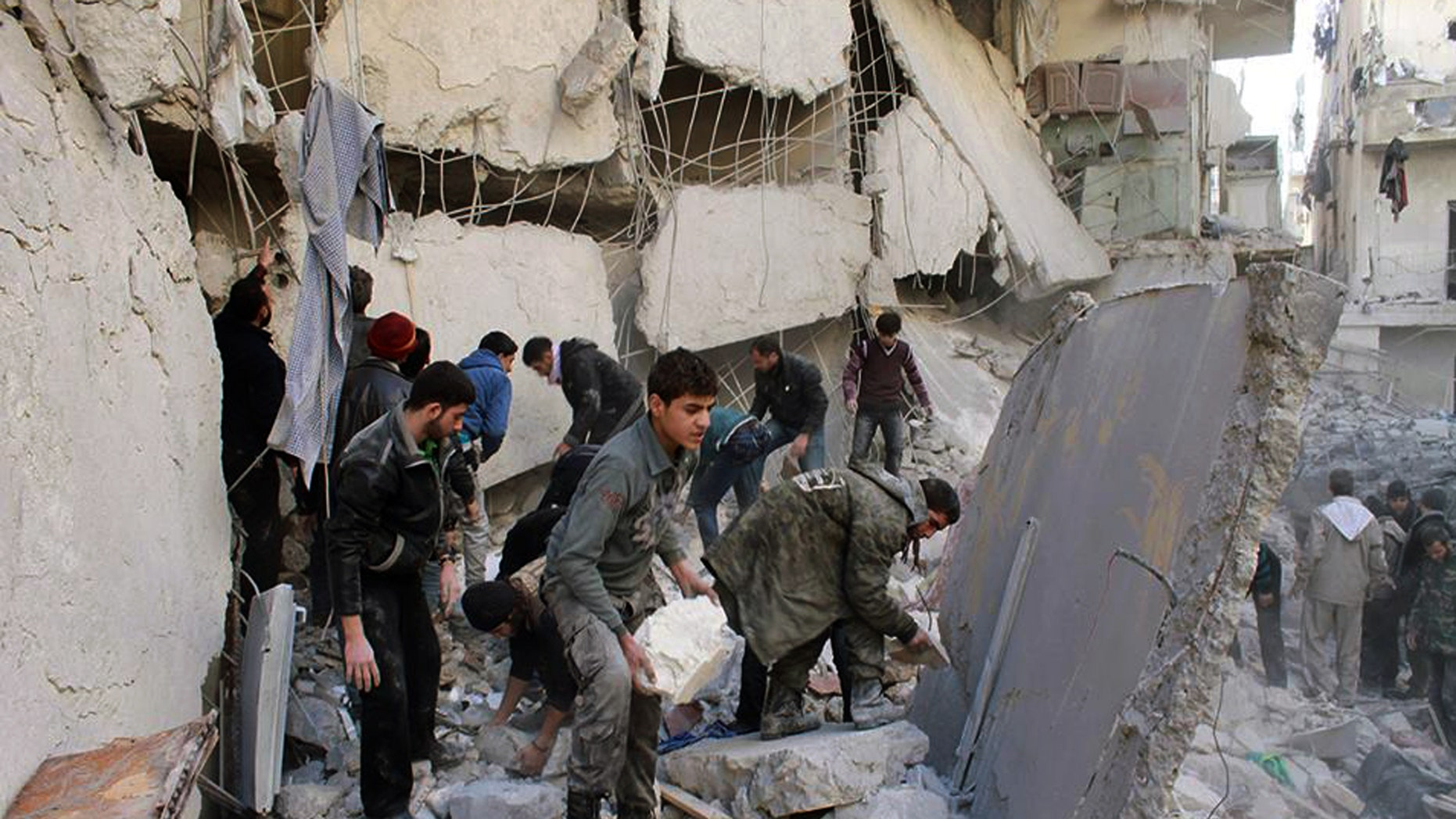 Jan. 31, 2014: In this citizen journalism image provided by Aleppo Media Center (AMC), an anti-Bashar Assad activist group, which has been authenticated based on its contents and other AP reporting, Syrians inspect the rubble of destroyed buildings following a Syrian government airstrike in Aleppo, Syria.