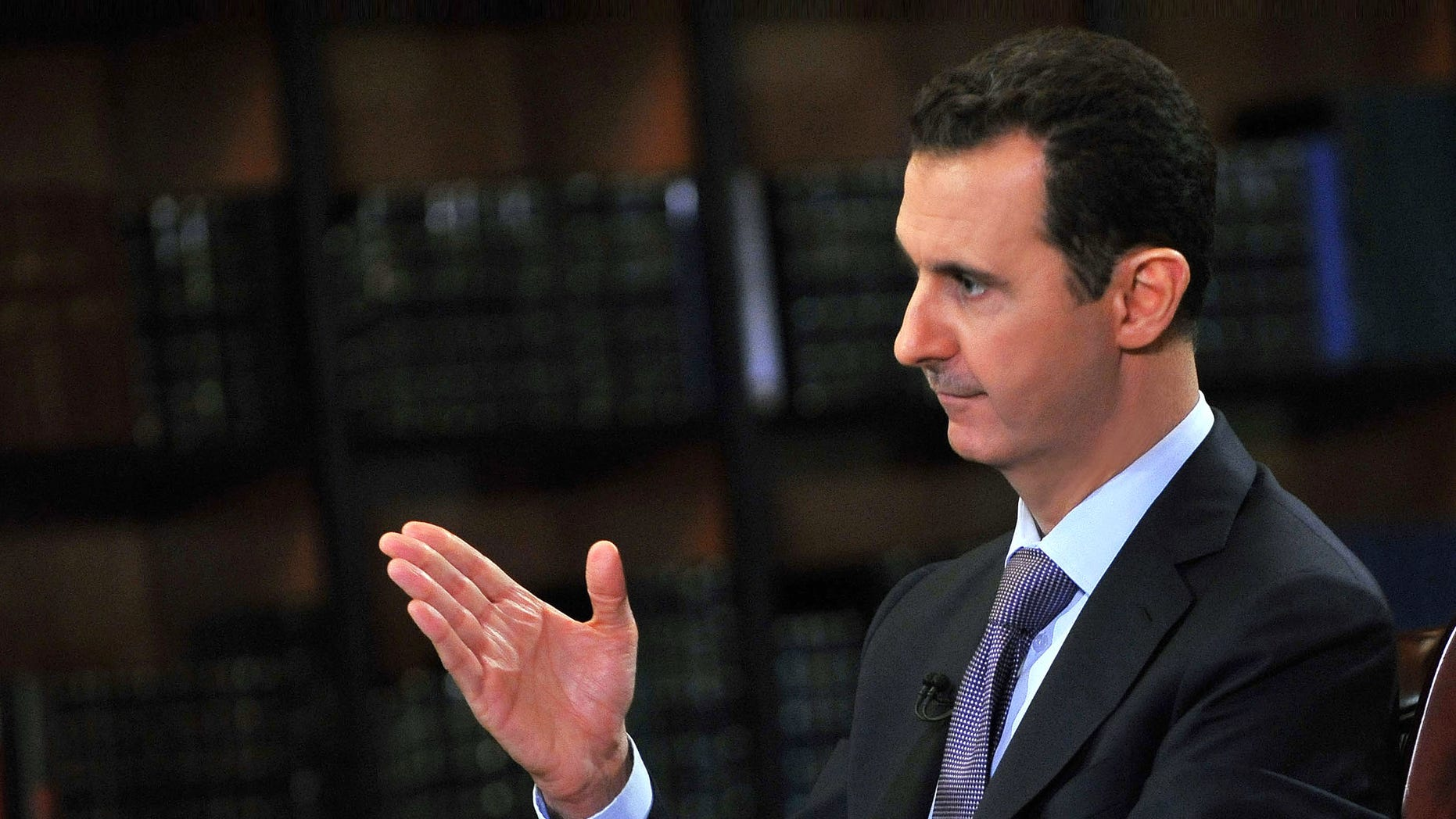 Sept. 29, 2013: In this photo, which AP obtained from Syrian official news agency SANA, has been authenticated based on its contents and other AP reporting, President Bashar Assad gestures as he speaks during an interview with Italy's RAI News 24 TV, at the presidential palace in Damascus, Syria.