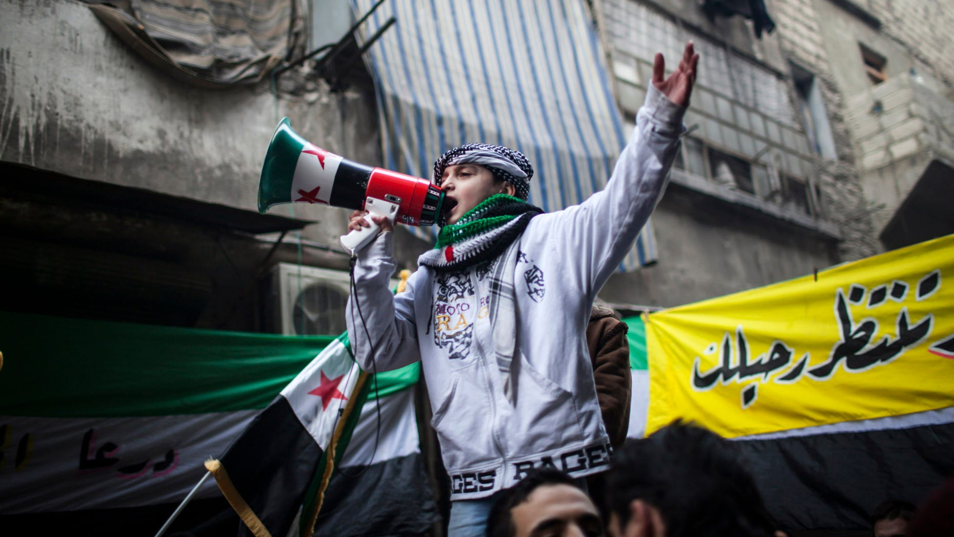 Jan. 4, 2012: A child uses a megaphone to lead others in chanting Free Syrian Army slogans during a demonstration in the neighborhood of Bustan Al-Qasr, Aleppo, Syria.
